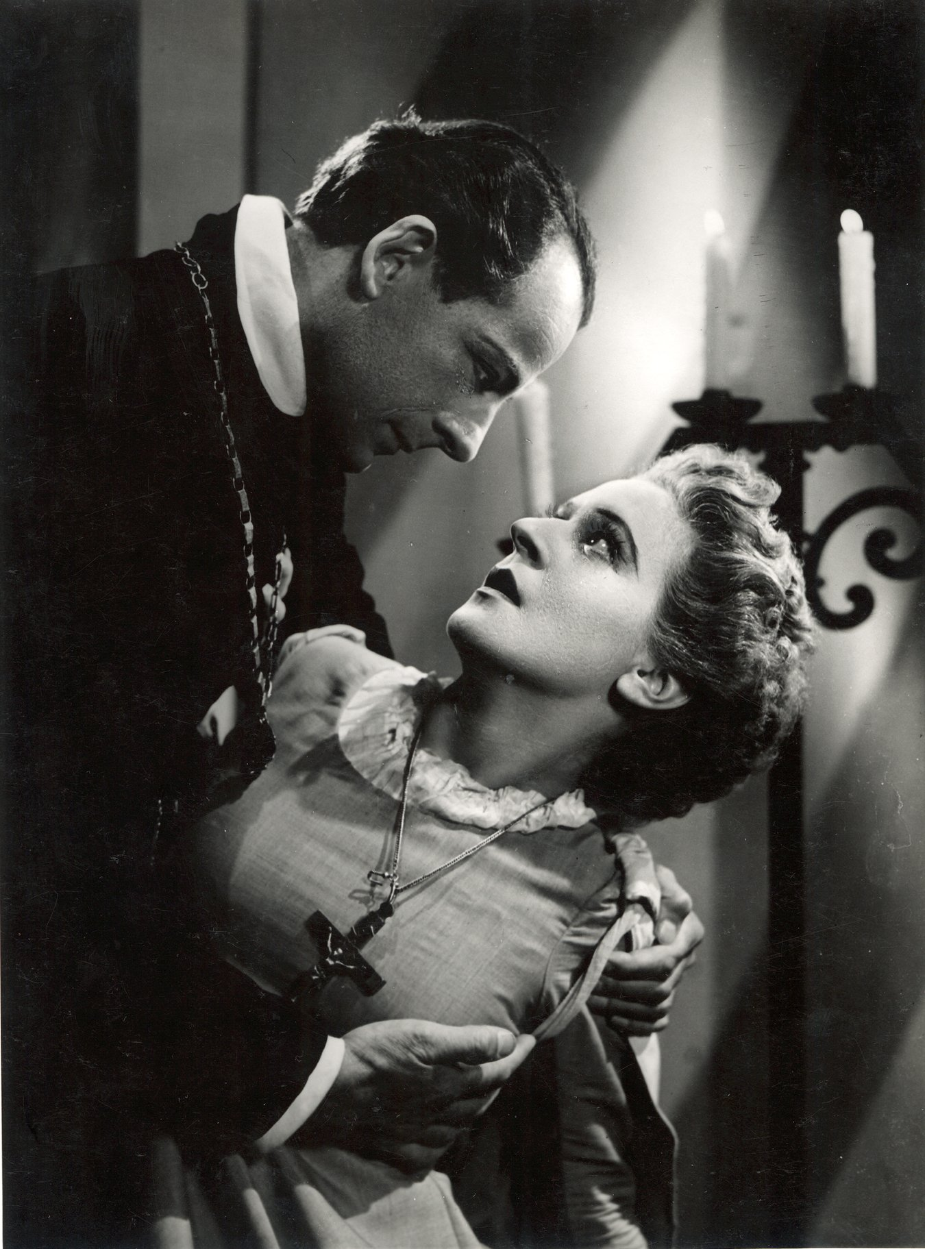 A man leans over a frightened young woman.