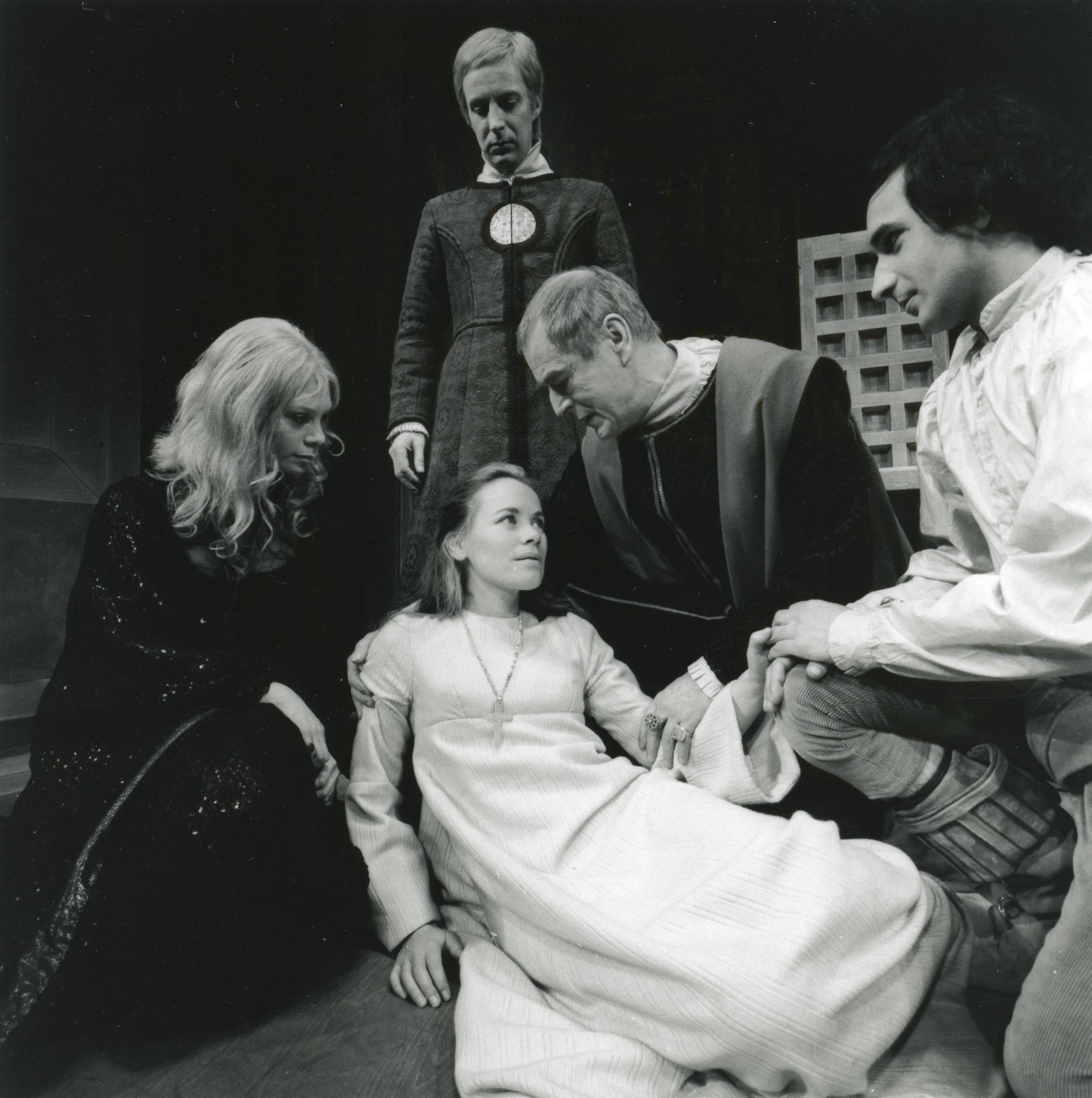 A woman in white lies on the floor surrounded by people.