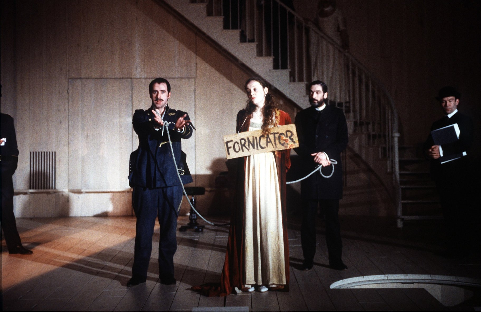 A woman in shackles with a sign saying 'Fornicator'