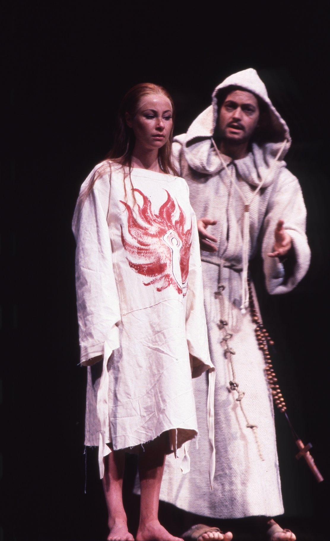 A man and woman in loose white robes.