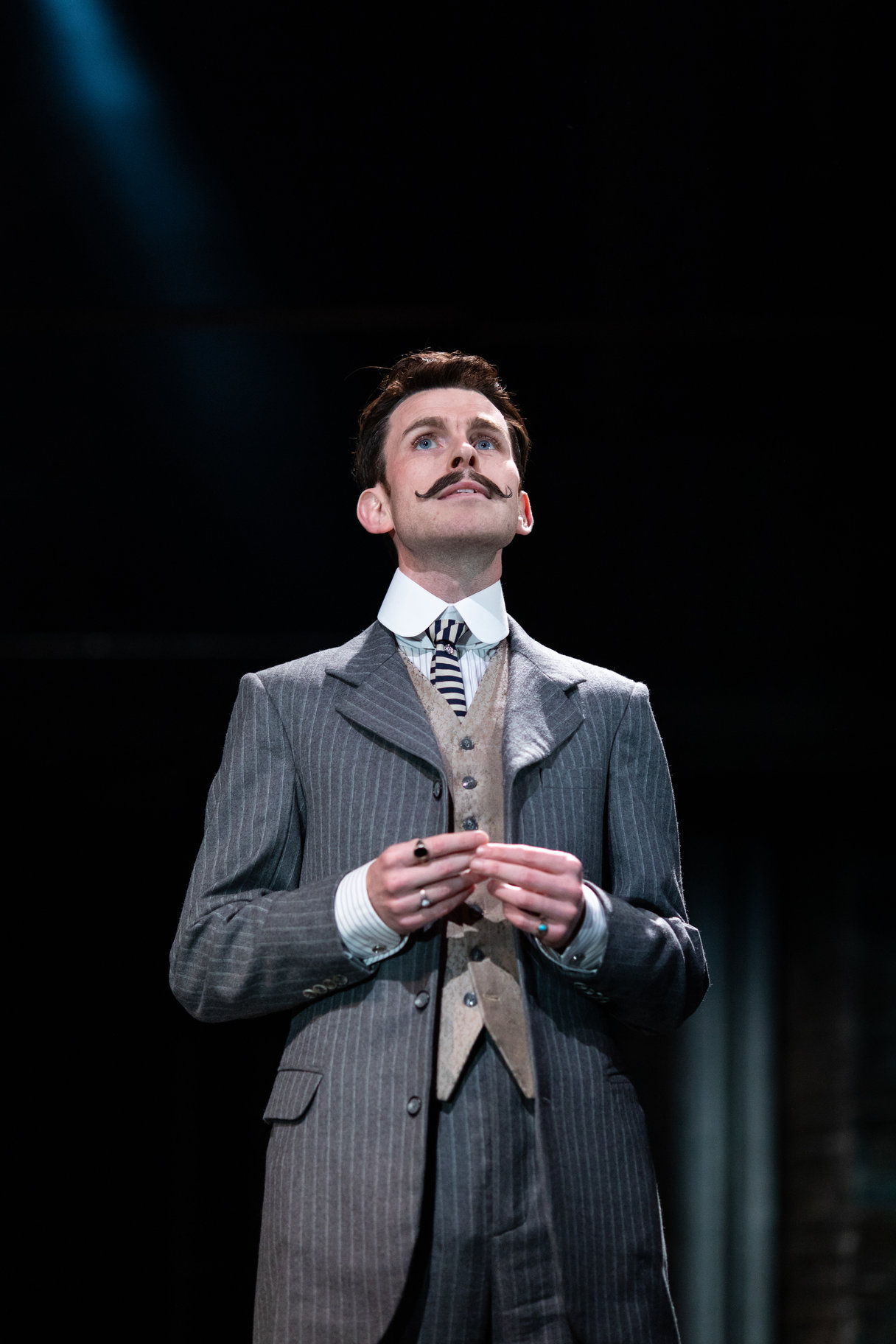 A man in a pin stripe suit with a curled moustache.