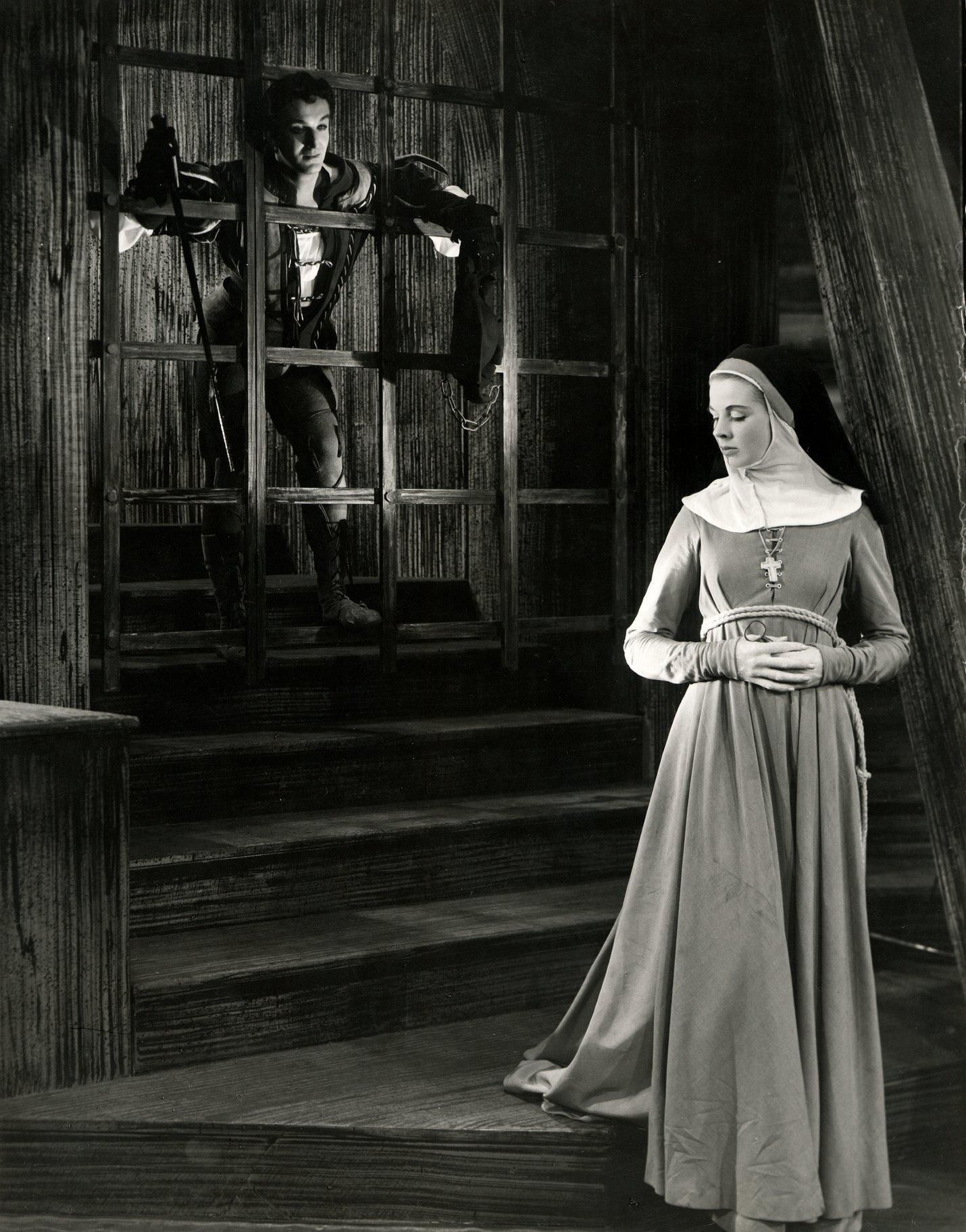 A man leans through bars to talk to a nun.