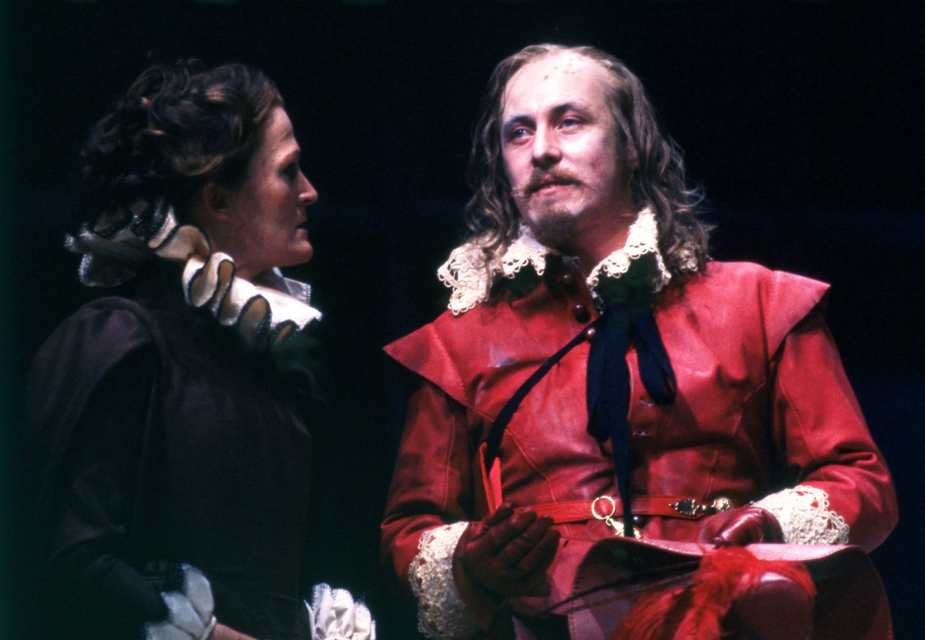 A woman in black talks to a man in a red suit.