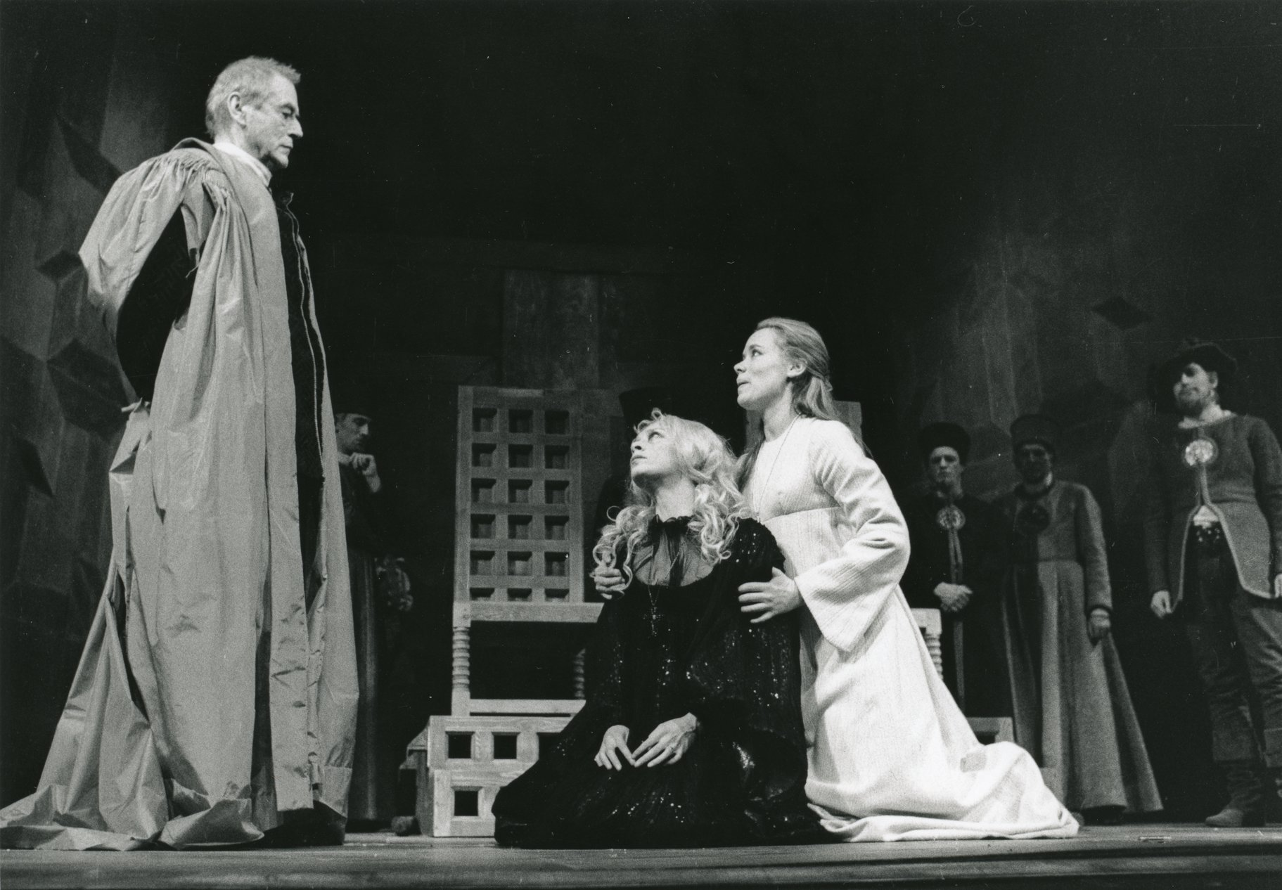 Two women kneel before a man in long robes.