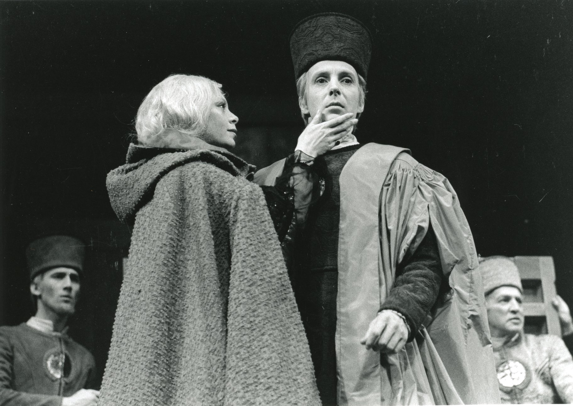 A woman in a cloak strokes a man's face.