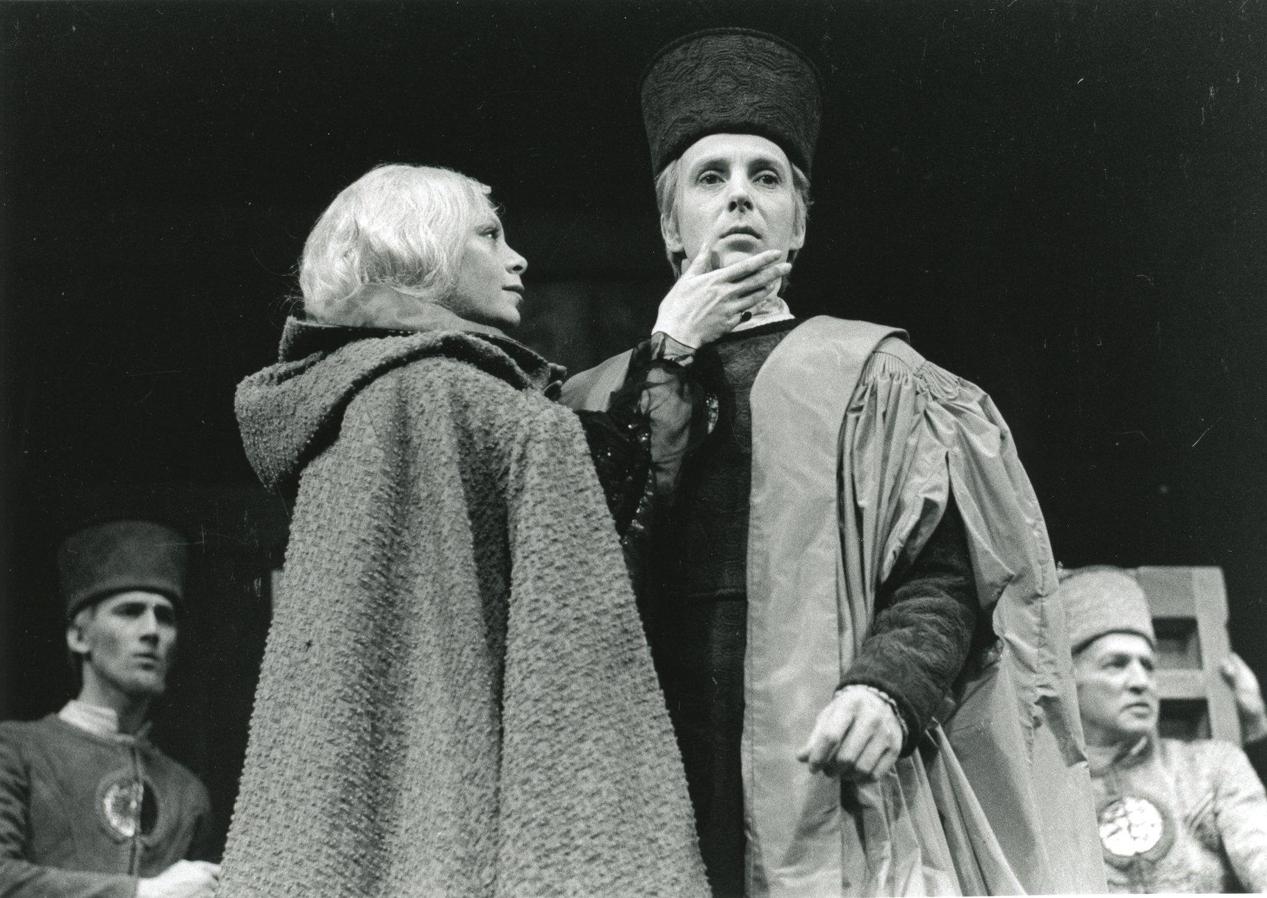 A woman in a cloak strokes a man's face.