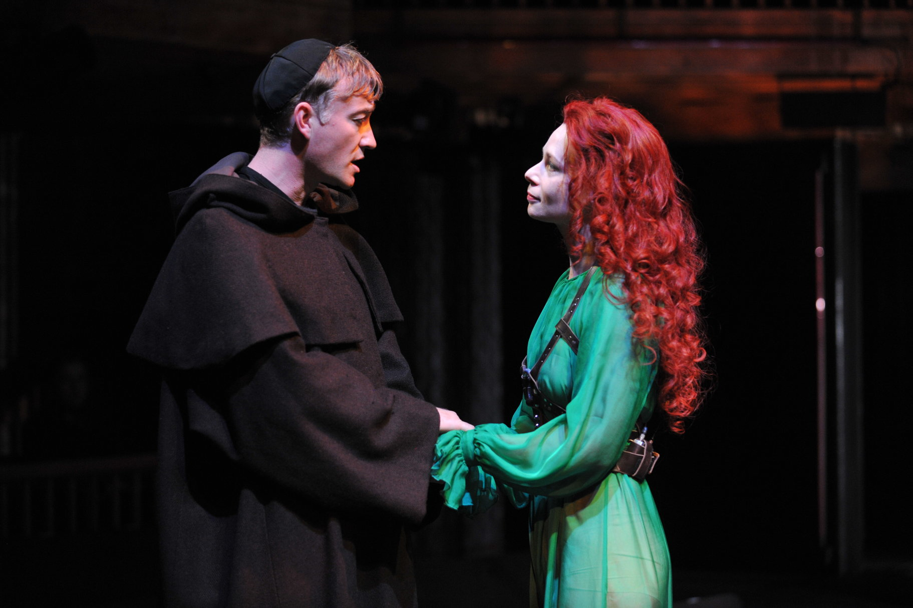 A man dressed as a monk holds the hands of a woman with bright red hair and a luminous green dress.