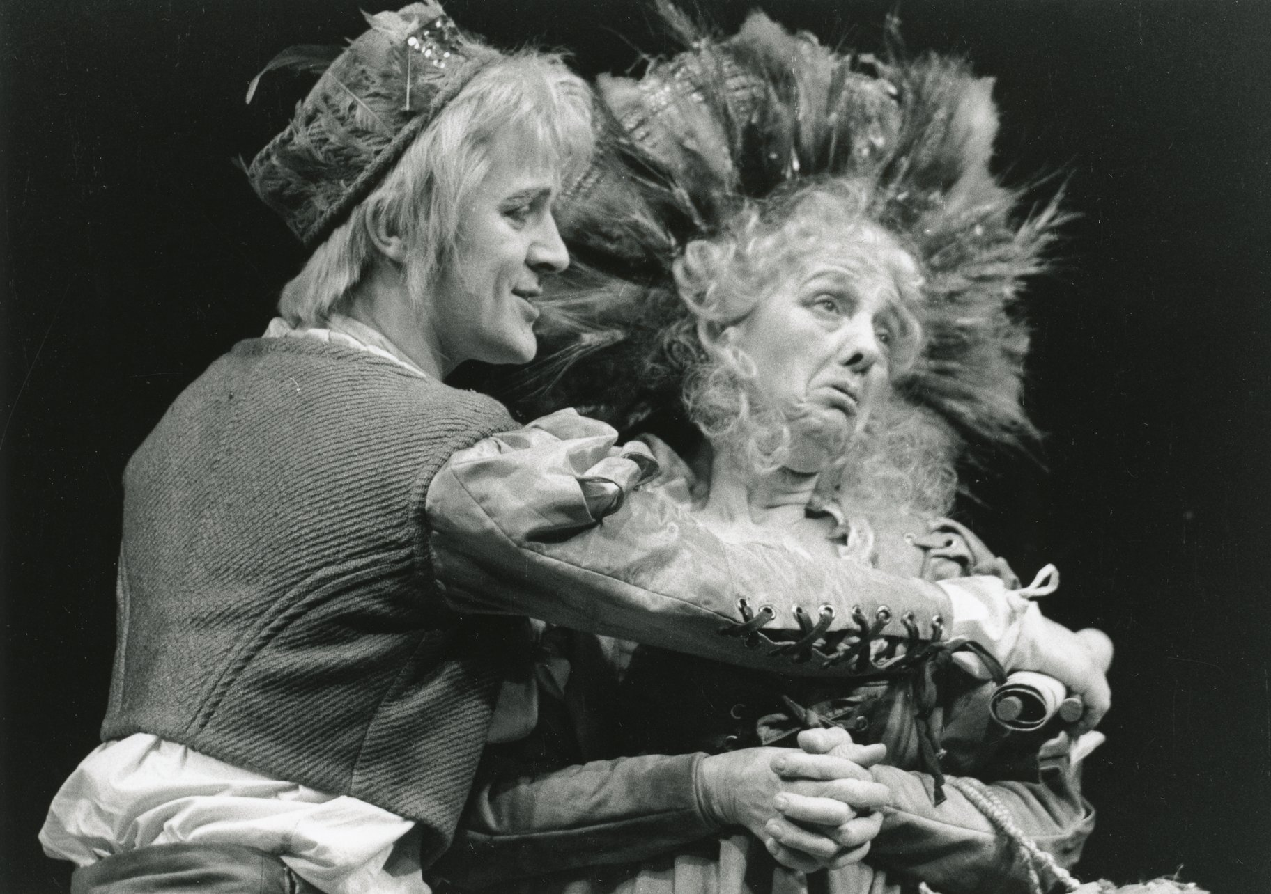 A man hugs a sad woman in a large feathered headdress.