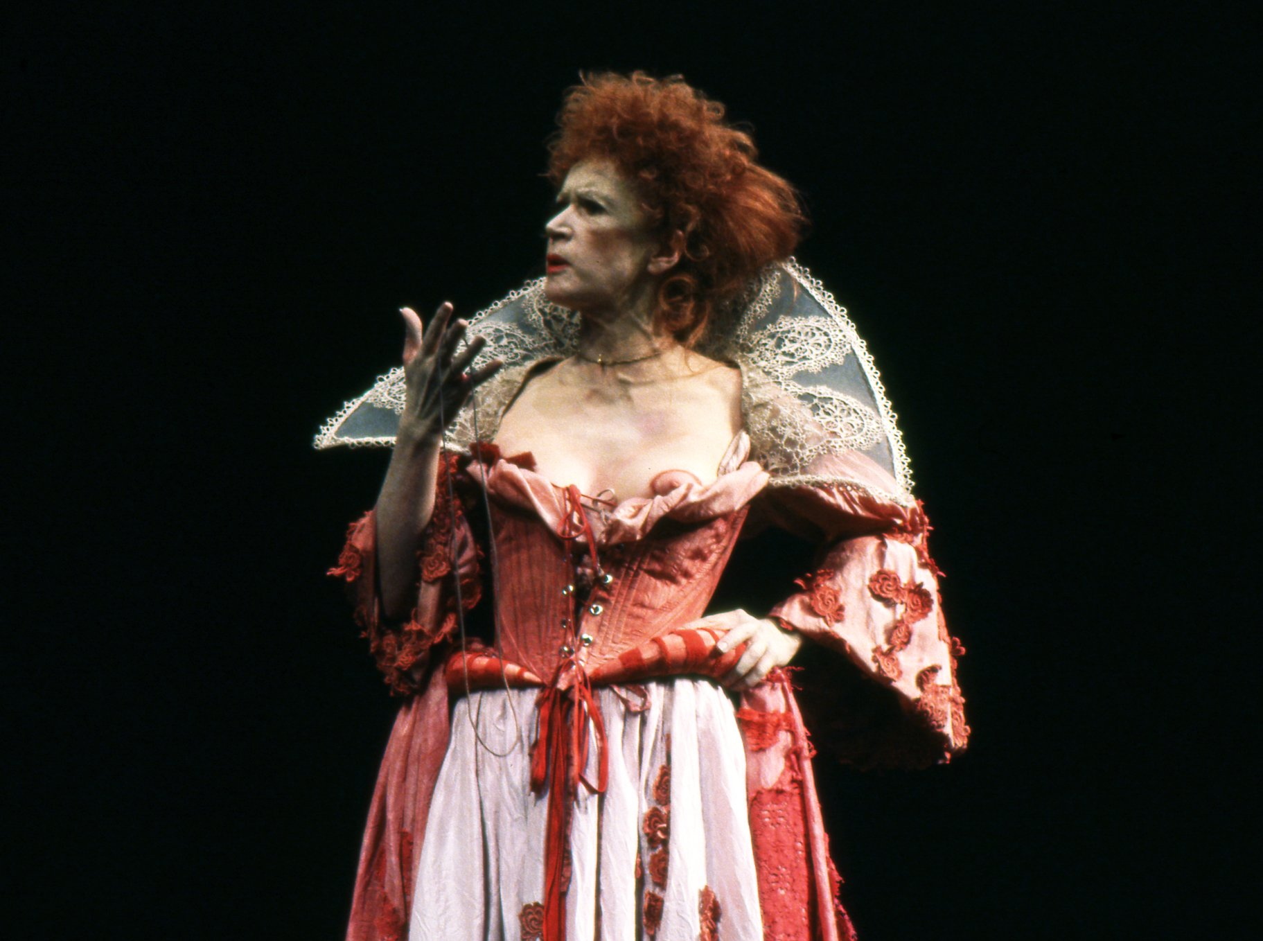 An older woman in a revealing red dress with heavy makeup.