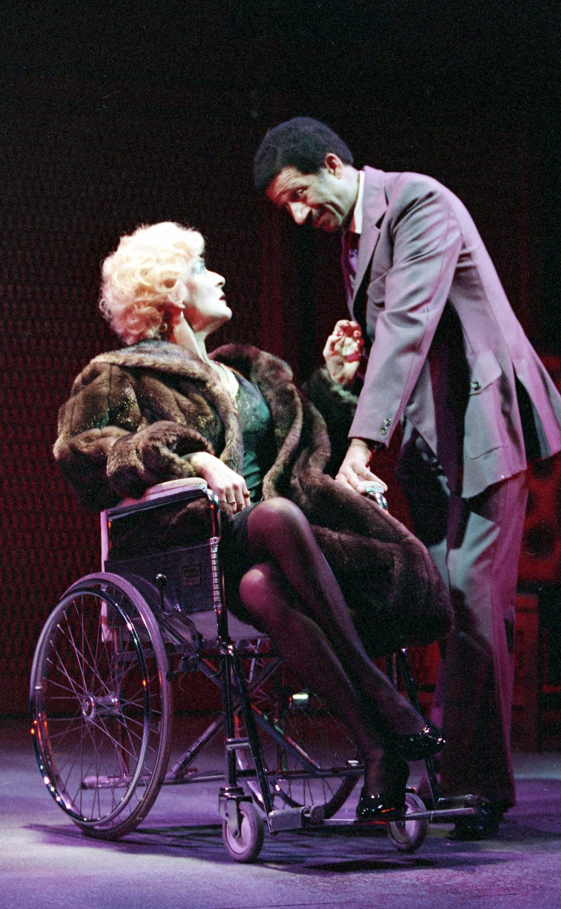 A woman in furs sits in a wheelchair.