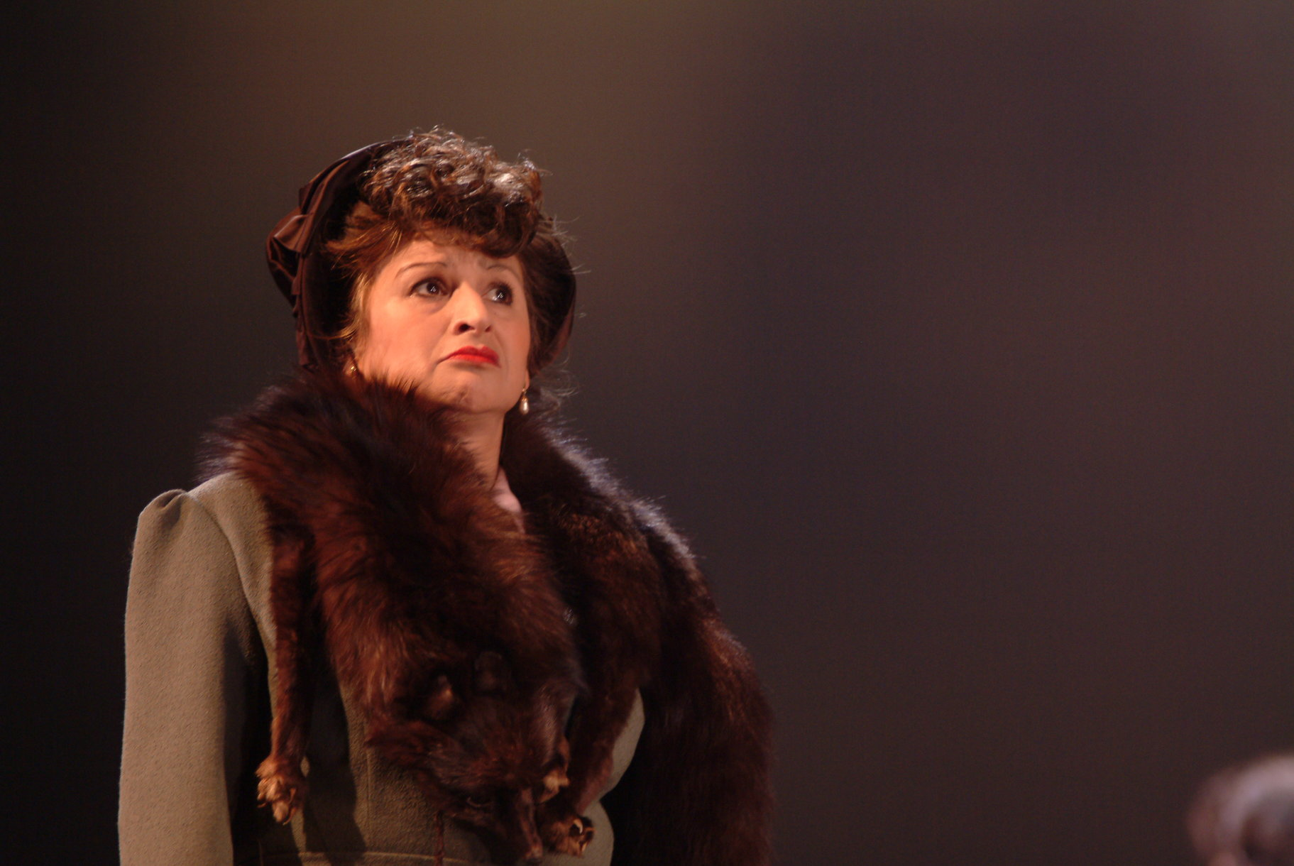 A woman in a jacket and fur stole.