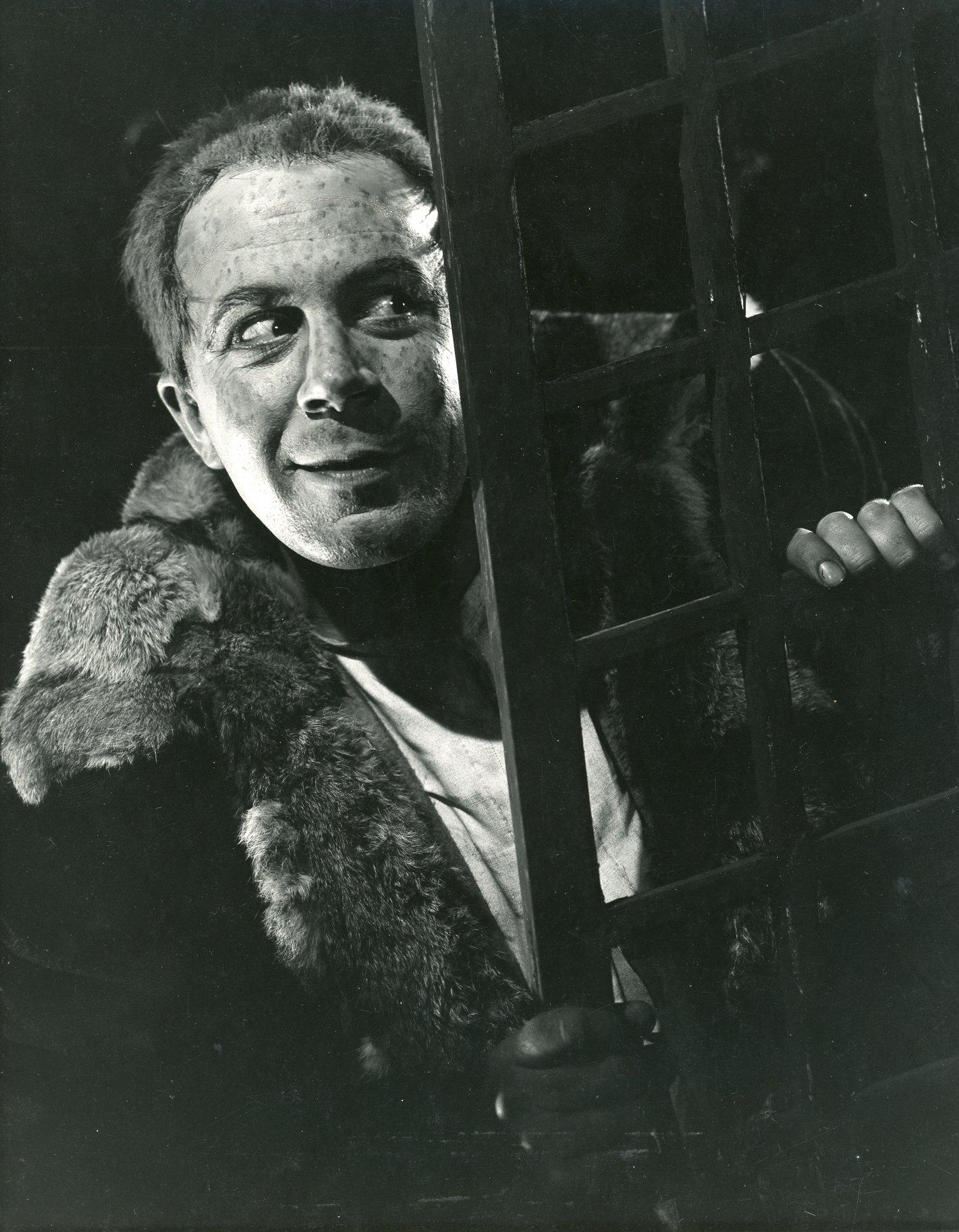 A man hides behind a wooden frame.