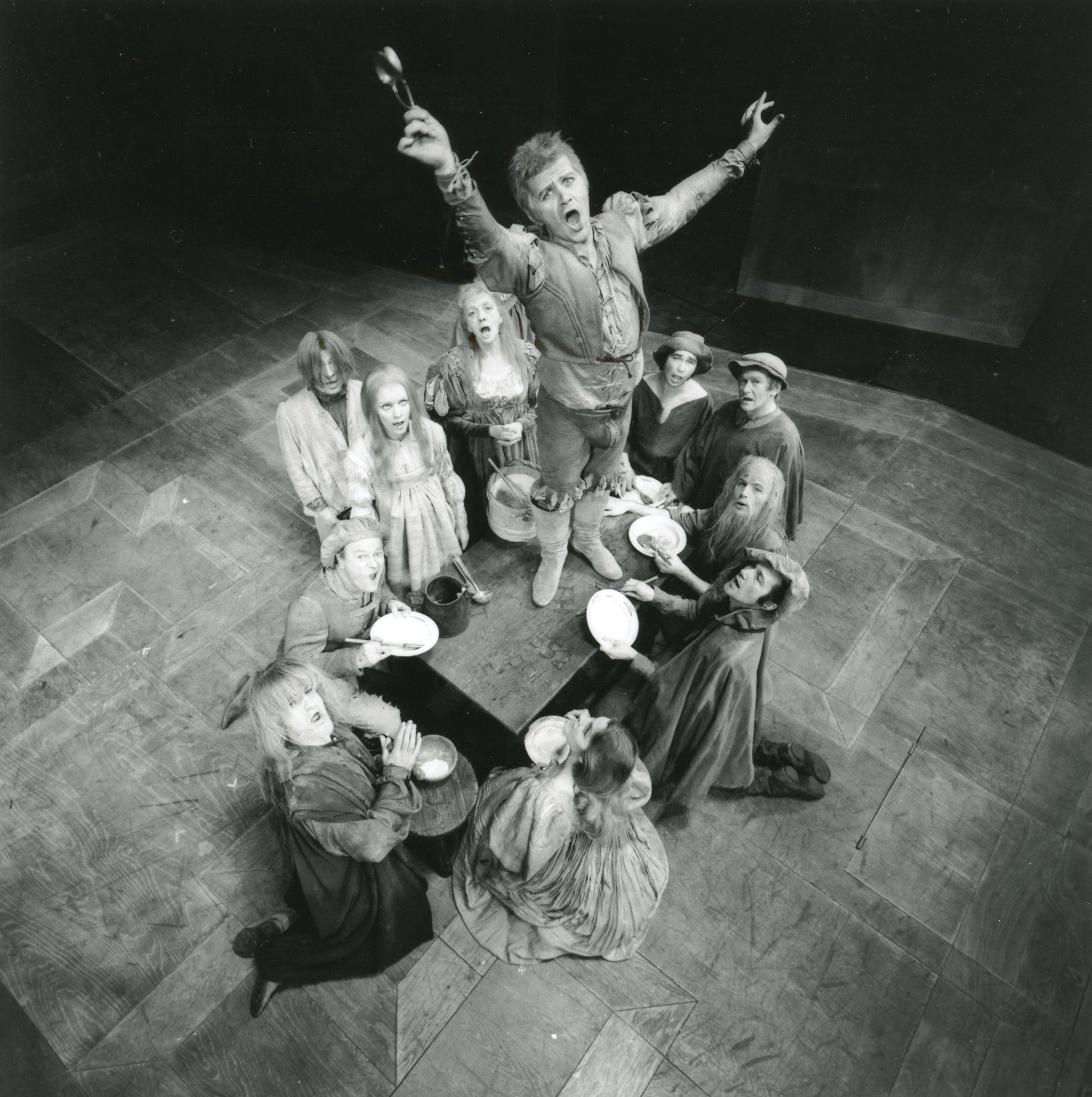 A man jumps onto a table surrounded by people.