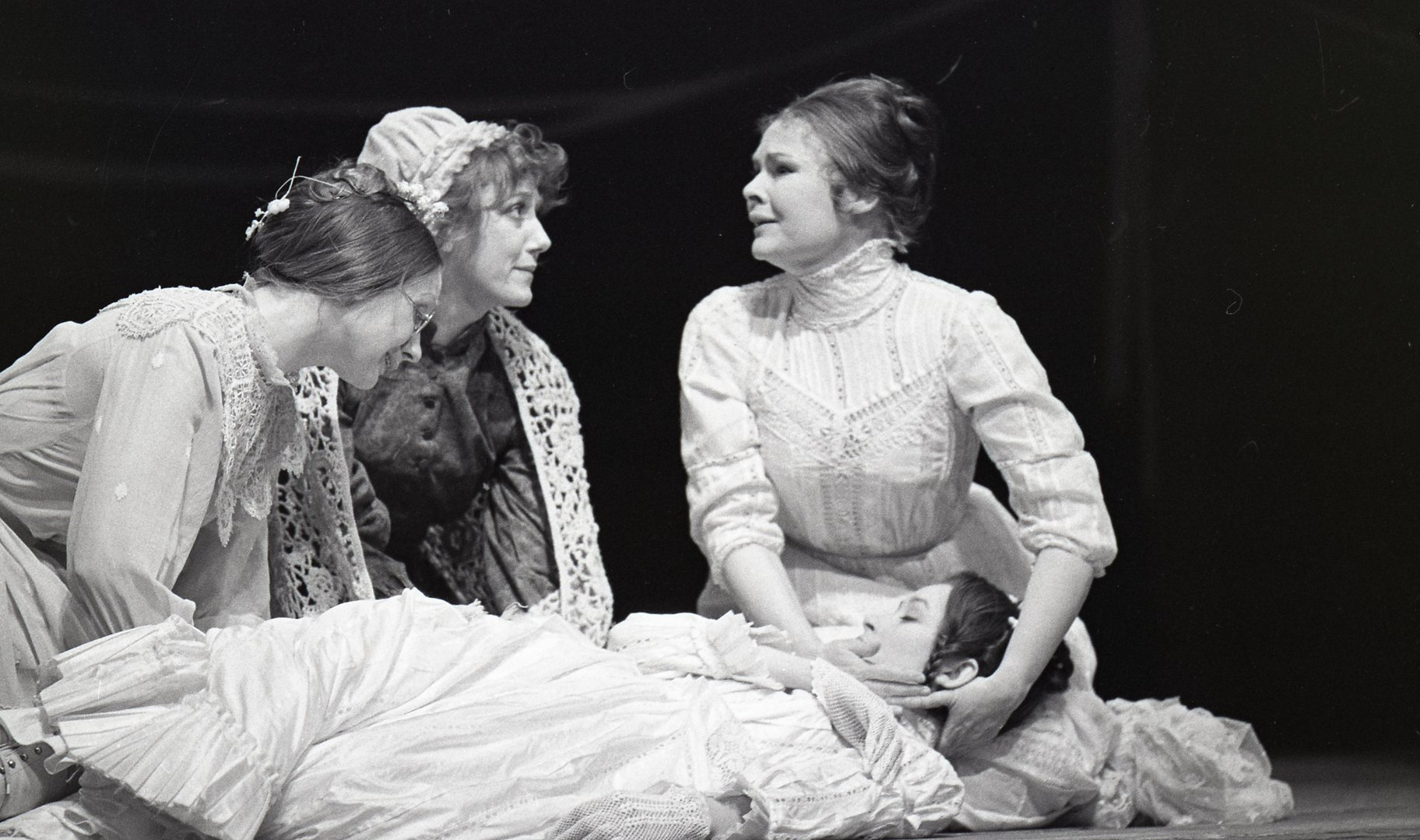 Three women surrounded a fainted woman, dressed in white.