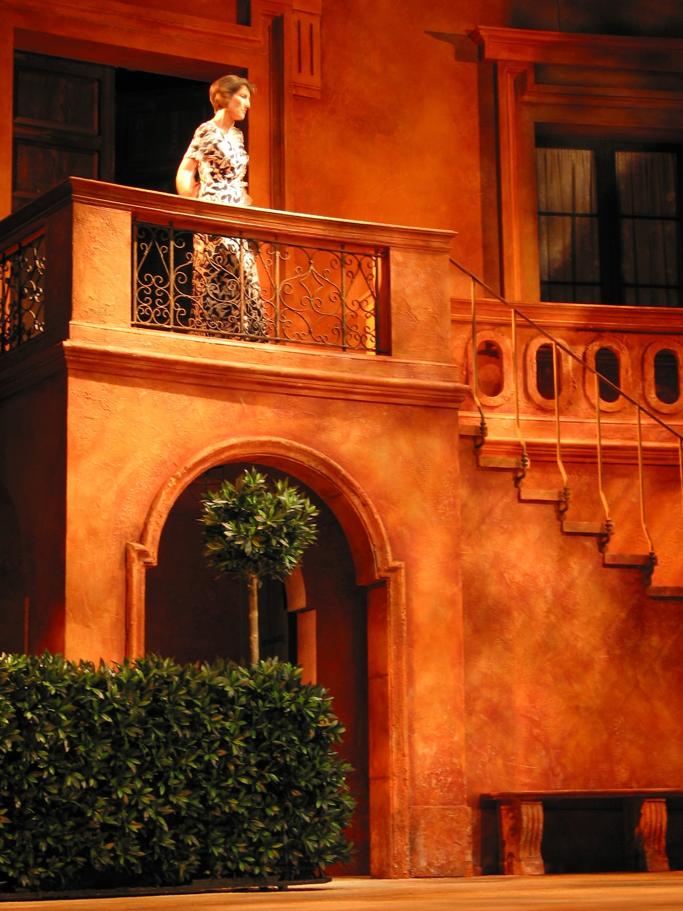 A woman on a balcony in a Mediterranean setting.