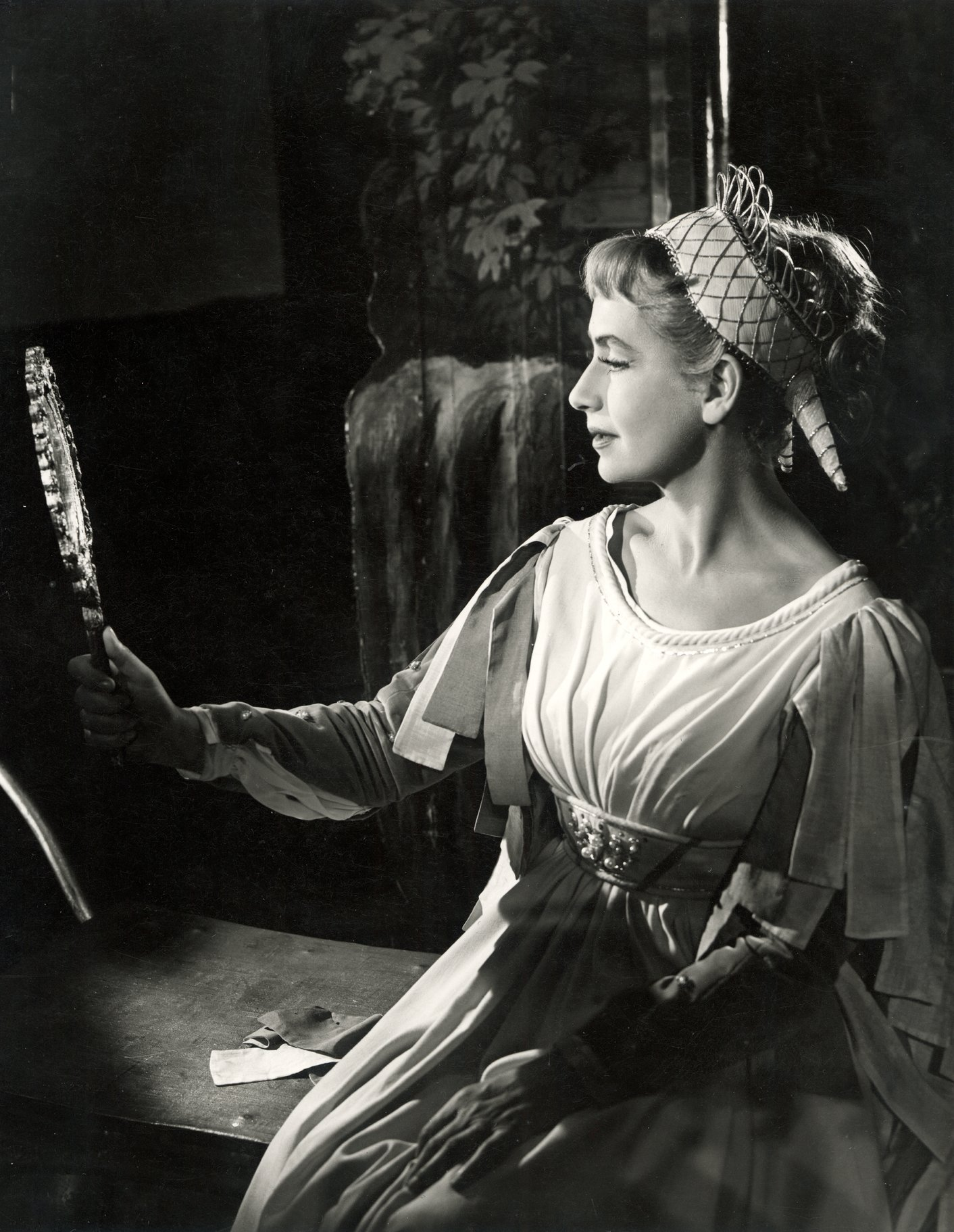 Peggy Ashcroft as Beatrice, looking at herself in a hand mirror.