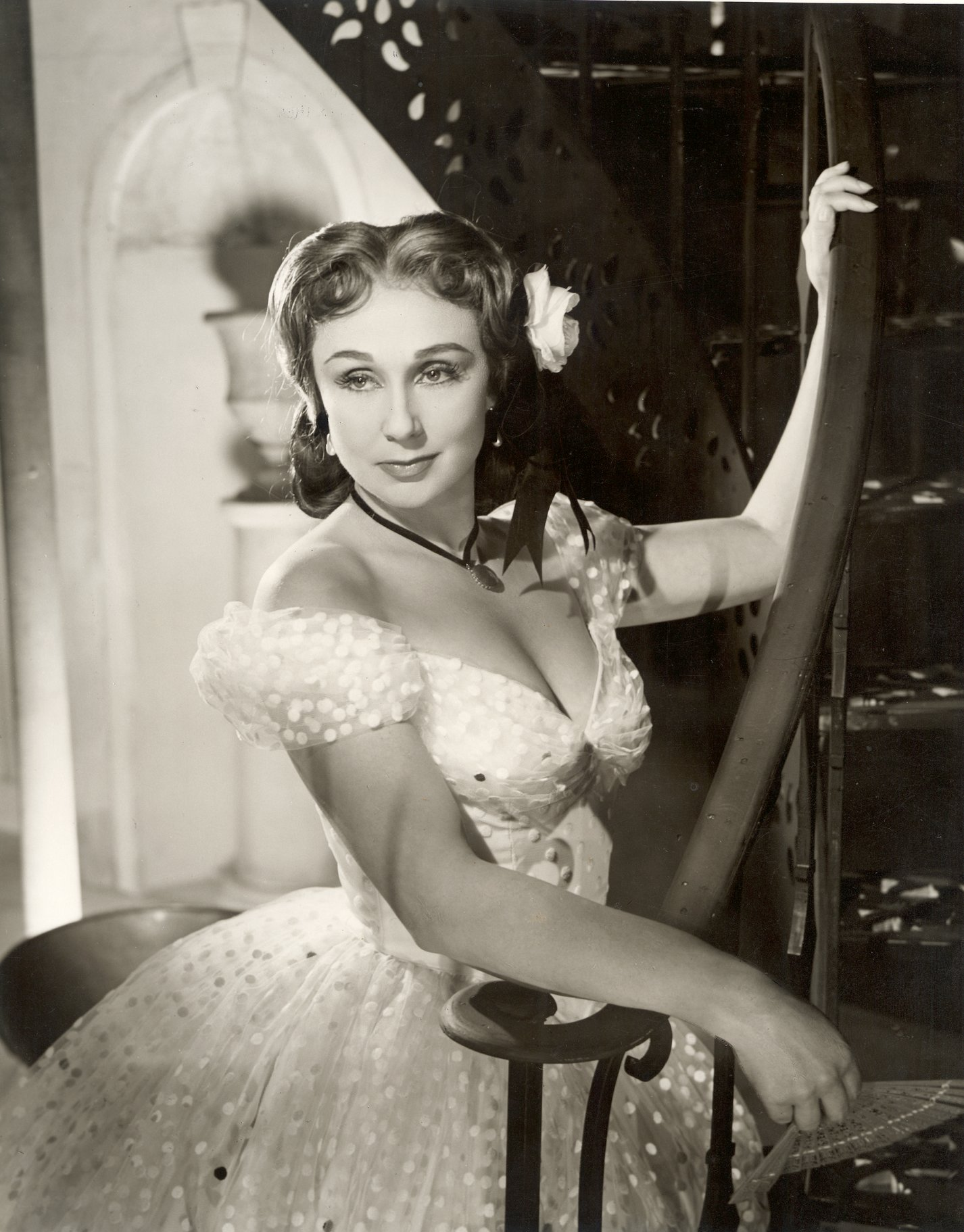 Googie Withers as Beatrice, wearing a low cut white dress and a white rose in her hair.