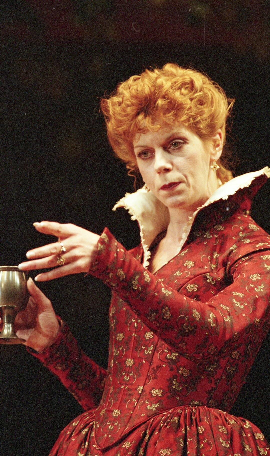 Siobhán Redmond as Beatrice in a red neck with a high collar.