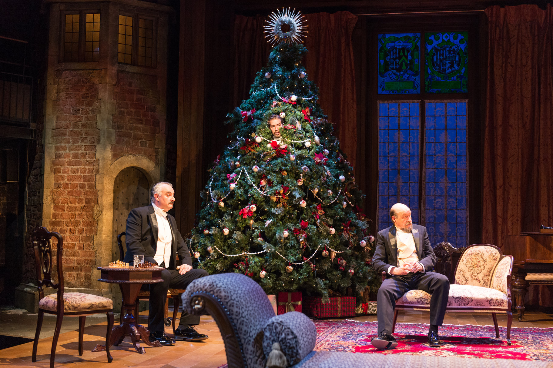 Two men in tuxedos sit next to a Christmas tree, which a man peers out from.