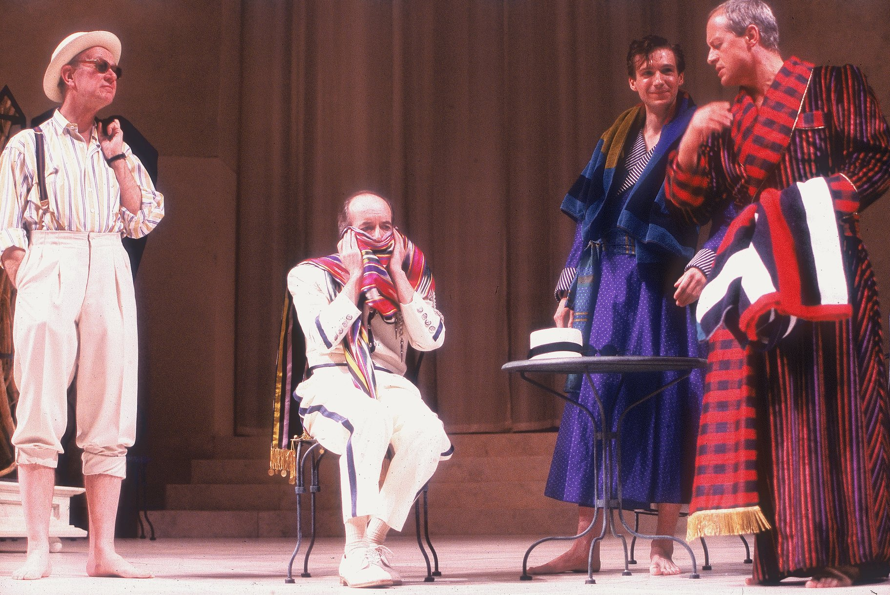 Three men in casual clothes and bathrobes talk around one sat on a chair with a scarf around his face.