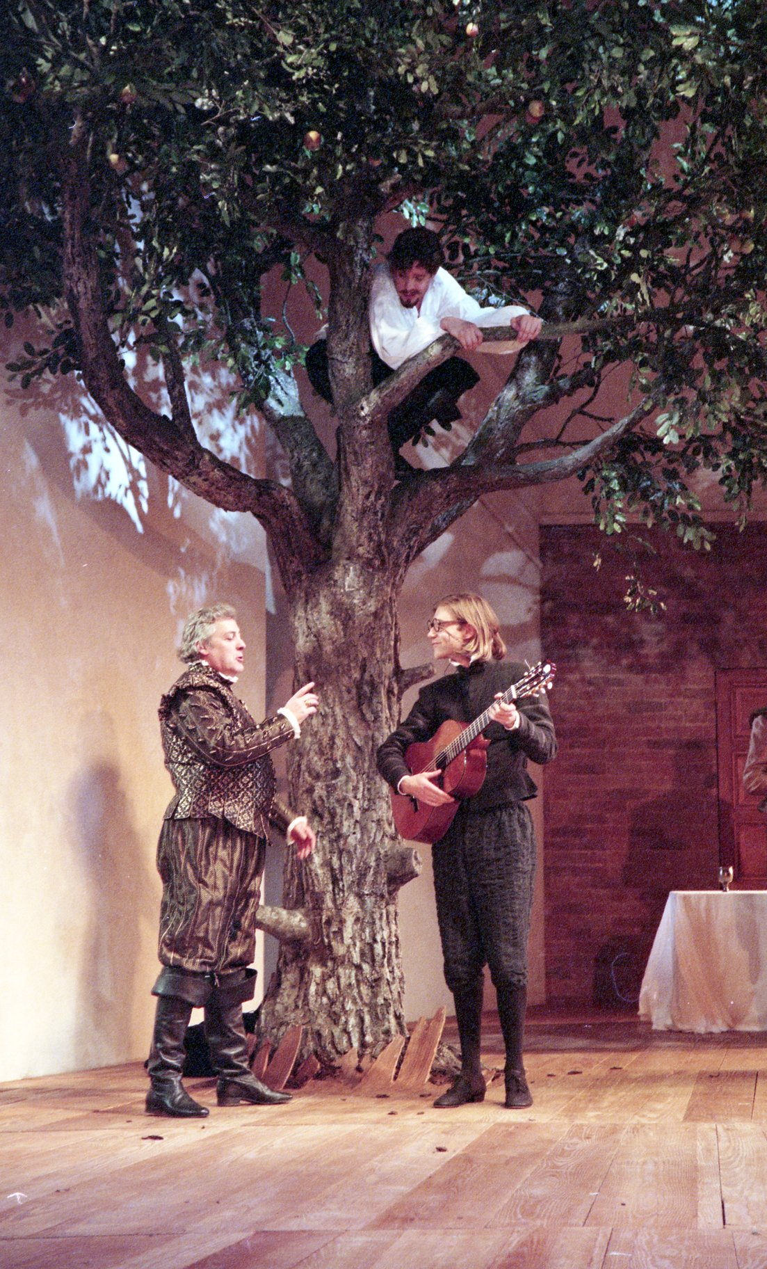 A man in a tree listens in to two men talking beneath him.