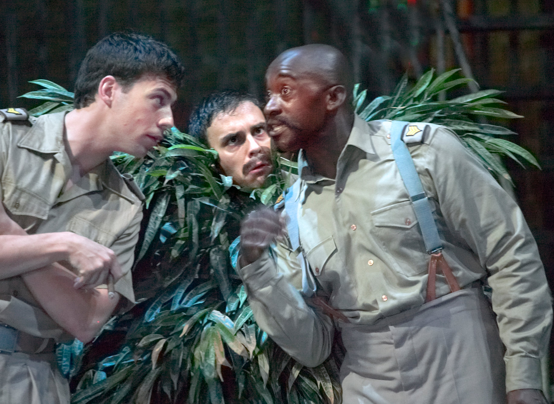 Two men talk in front of a man disguised as a bush.