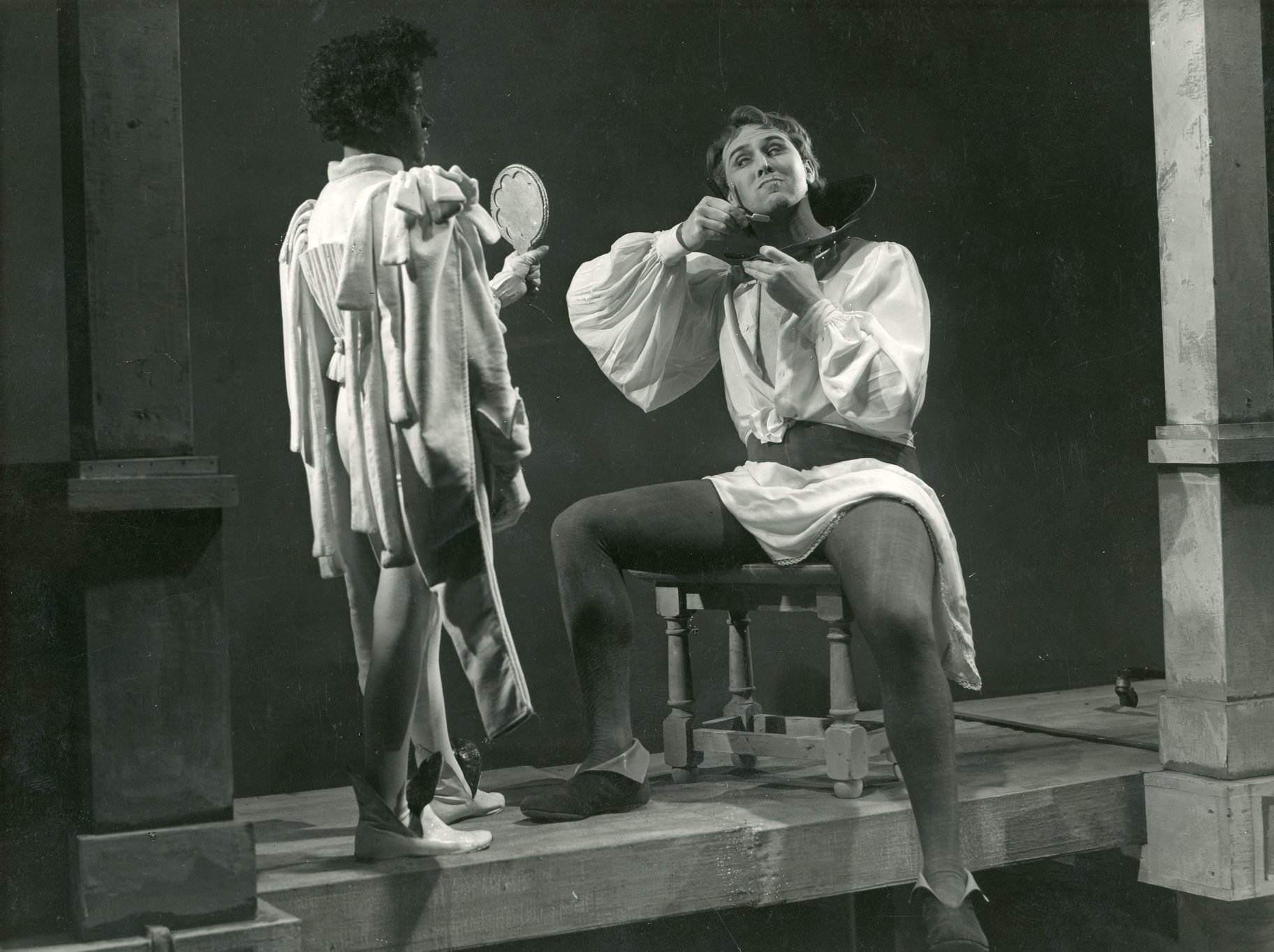 Benedick shaves as a servant holds up a mirror.