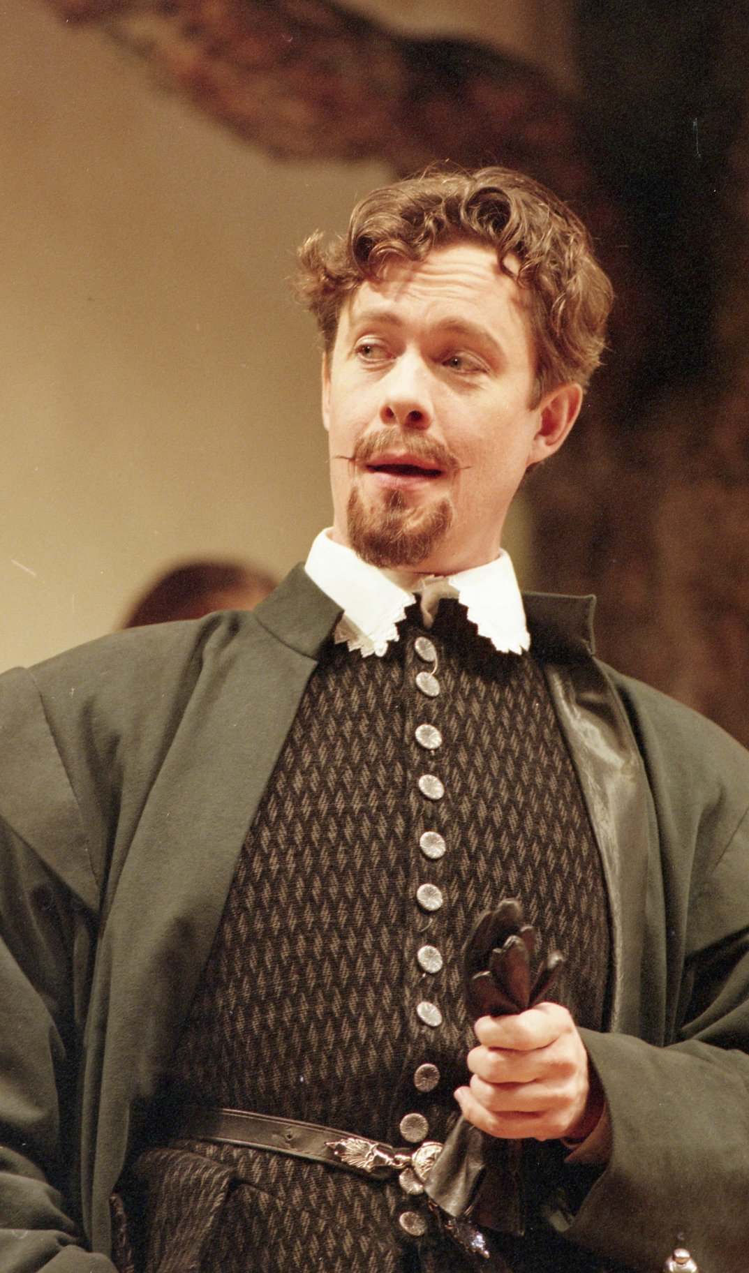 Benedick all in black and holding a pair of gloves.