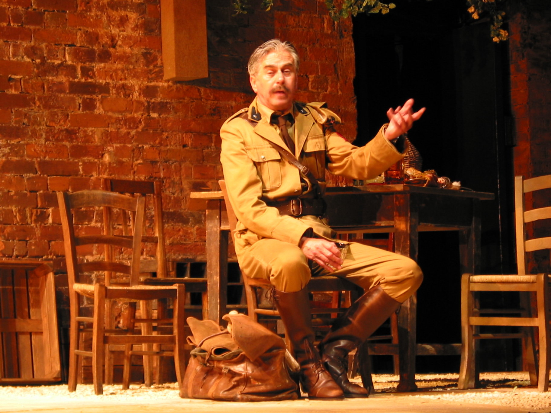 Benedick in a khaki suit and brown leather boots.