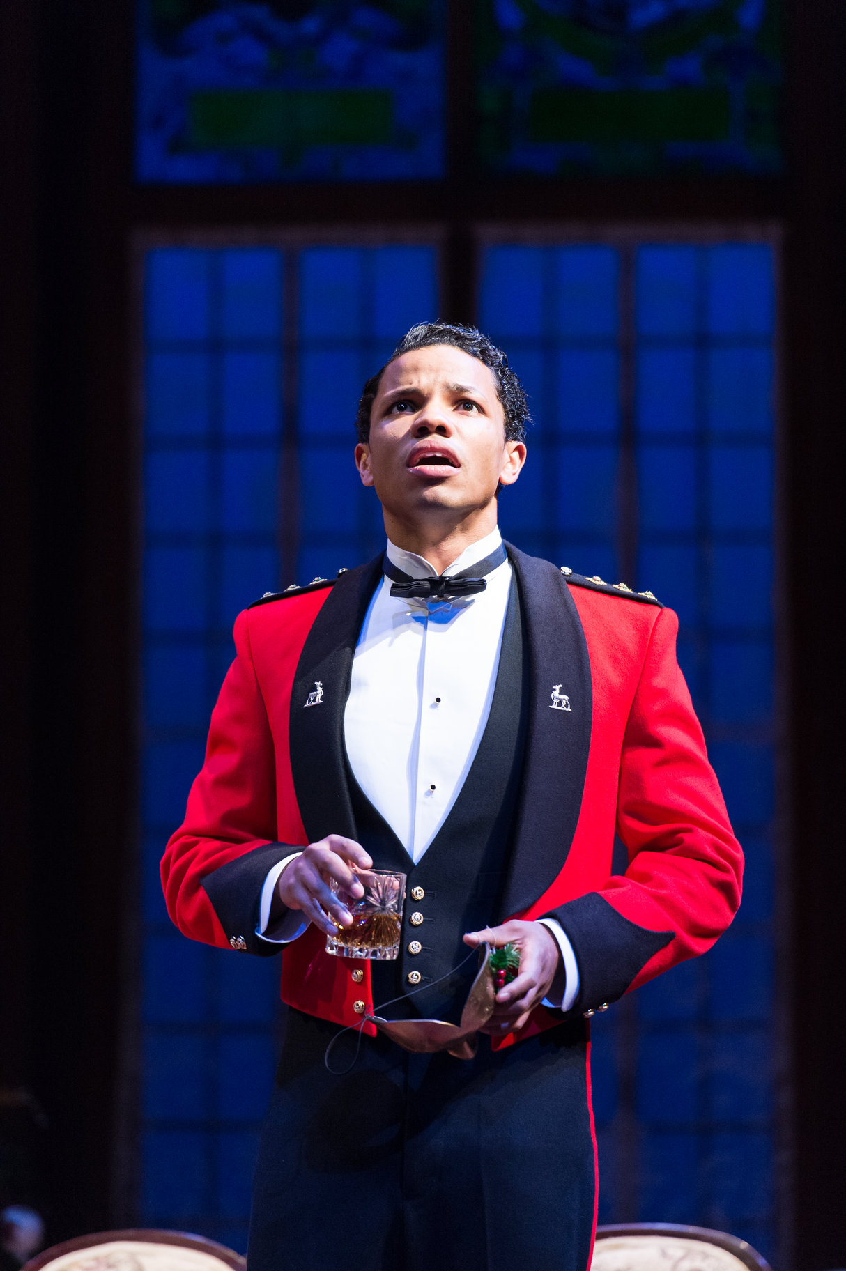 Tunji Kasim as Claudio in a red soldier's jacket.
