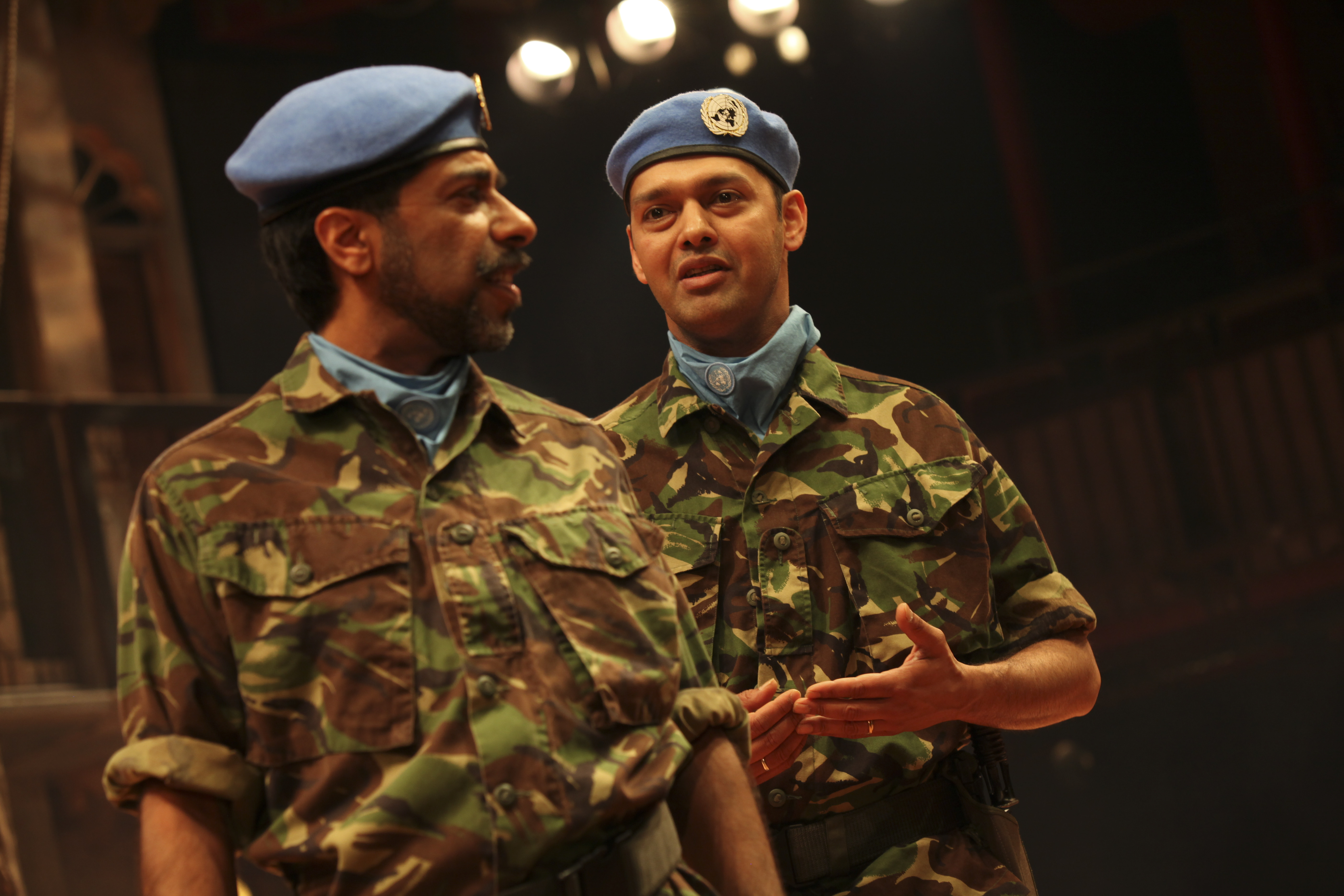 Two men in army fatigues and blue berets.