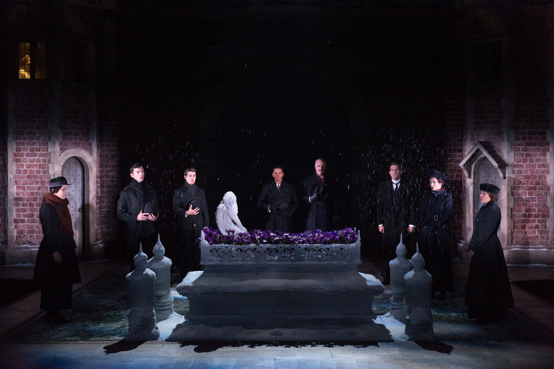 Mourners in black around a tomb.