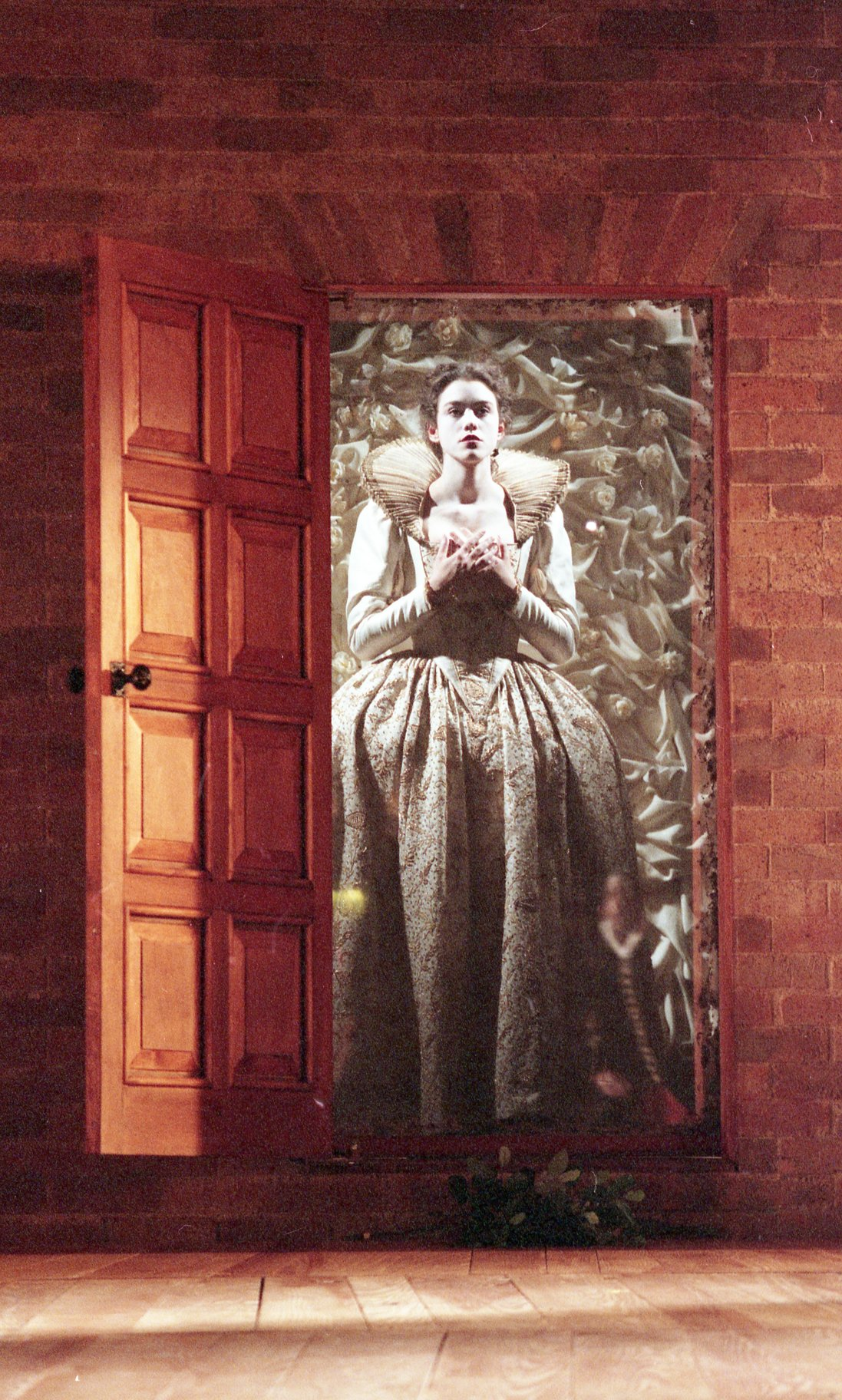 A woman in white lies behind a wooden door, much like a coffin.