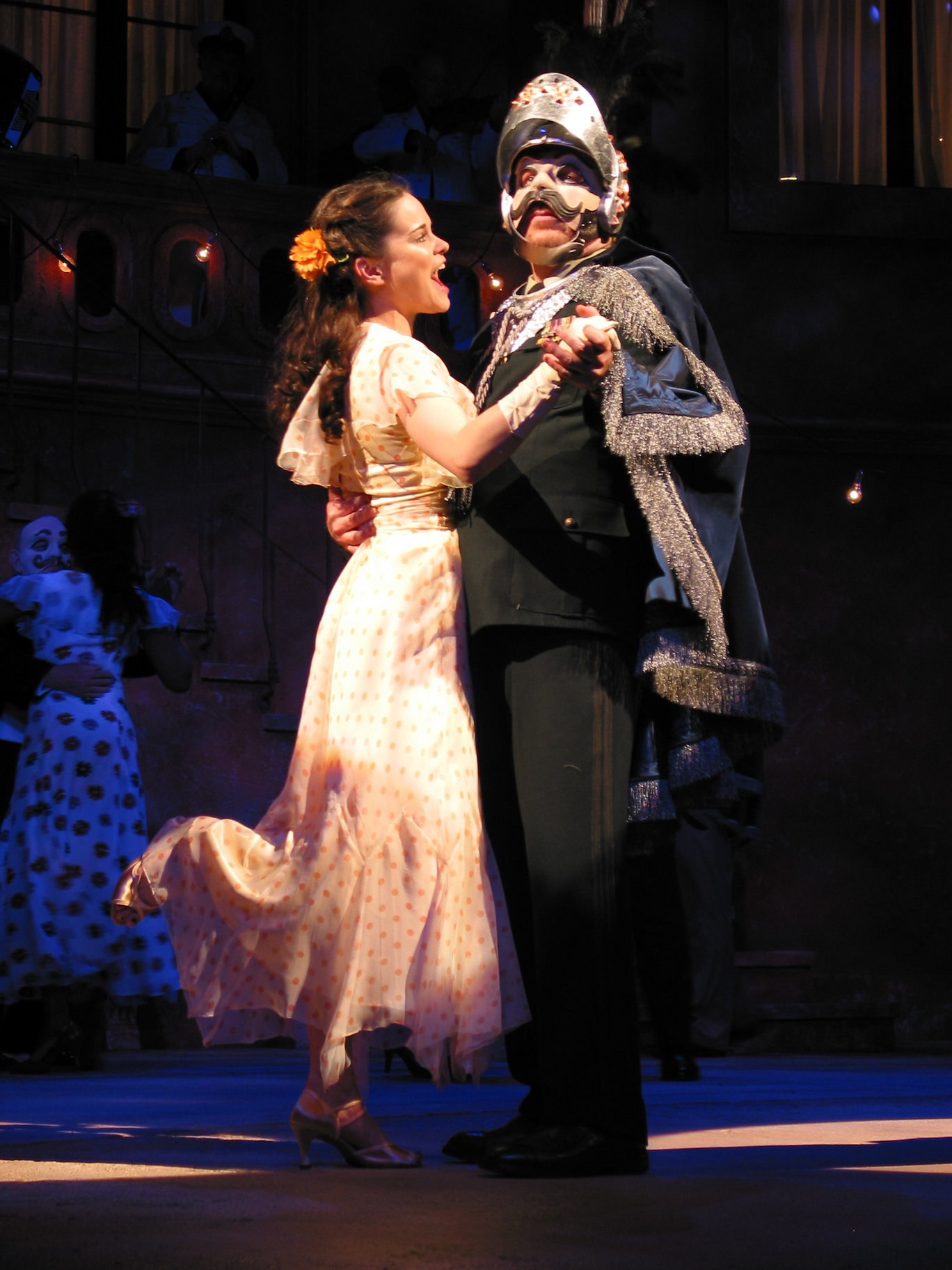 A woman dances with a disguised man at a masked ball.