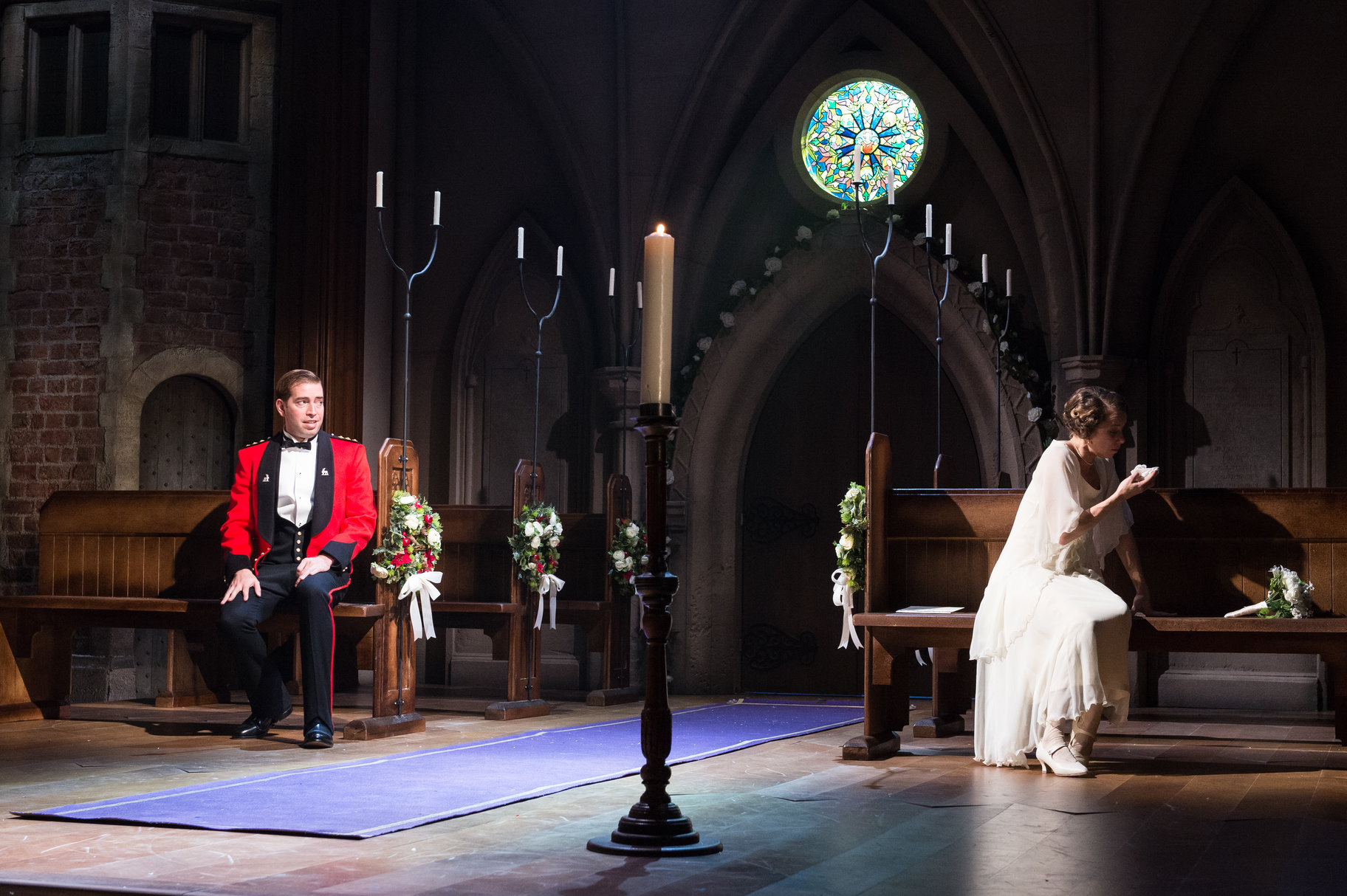 A man looks at a crying woman in a church.