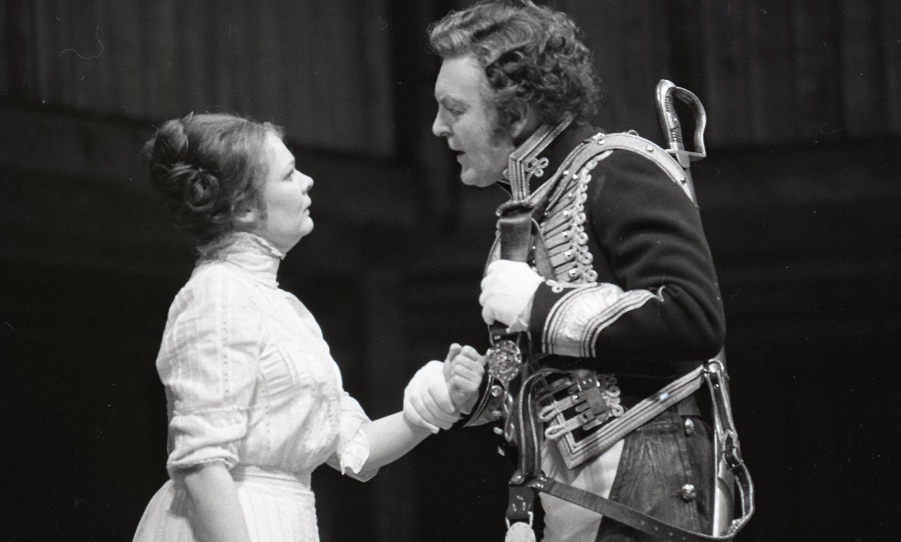 Benedick, in full uniform, grabs hold of Beatrice's arm.
