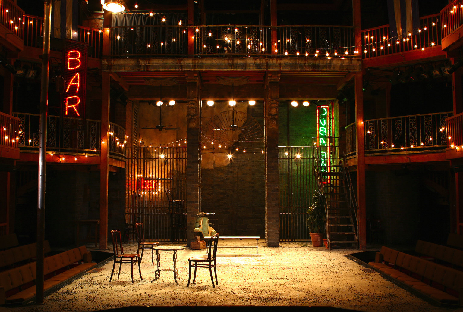 A stage set with a table and some chairs, with lights around the balcony.