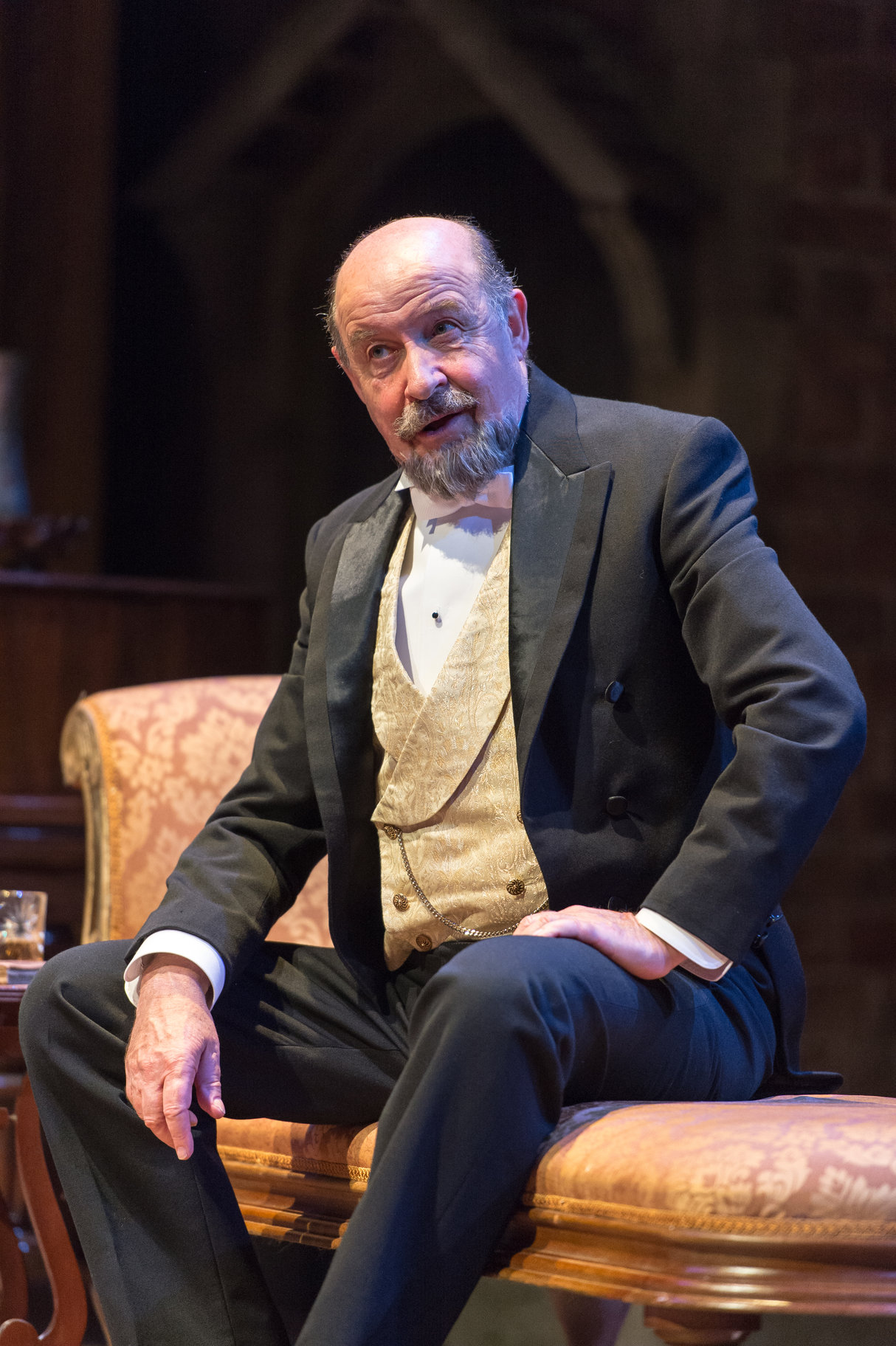 David Horovitch as Leonato in evening wear, sat on a chaise longue.