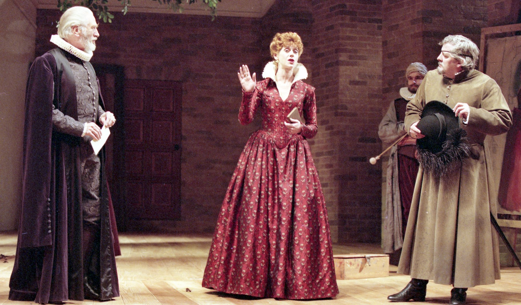 A woman in a red dress talks to three men.