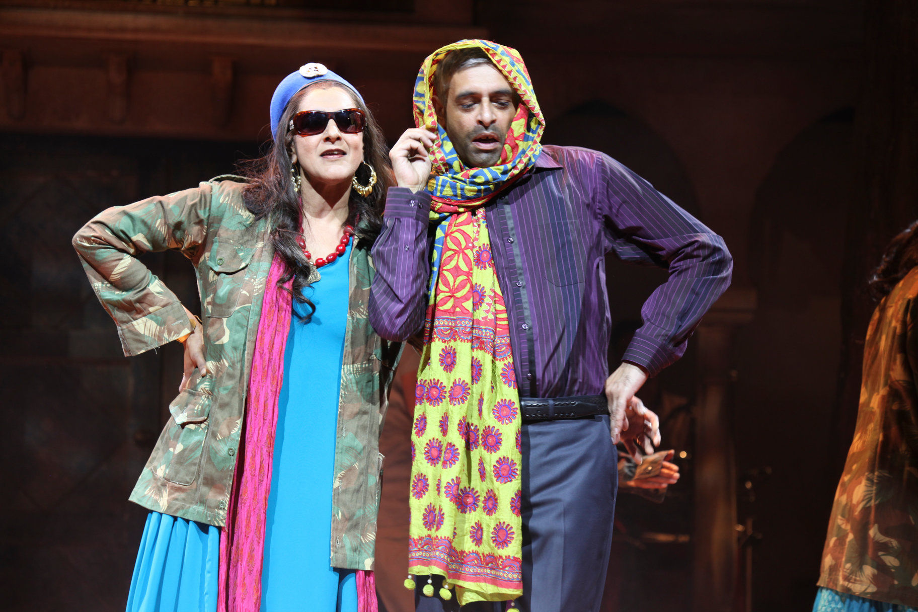 Beatrice and Benedick wearing multicoloured clothes and scarves.