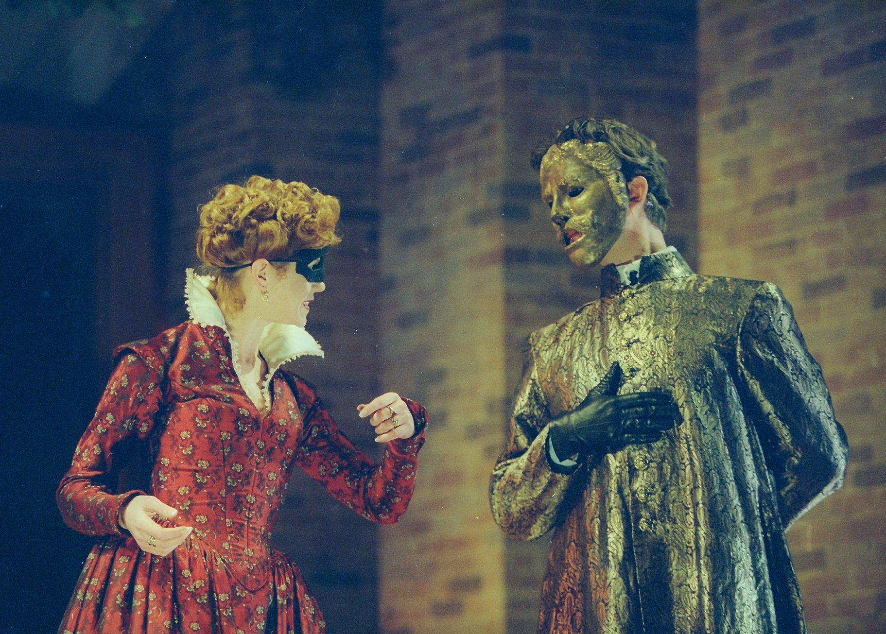 Beatrice in a red dress and black mask with Benedick in a gold tunic and mask.