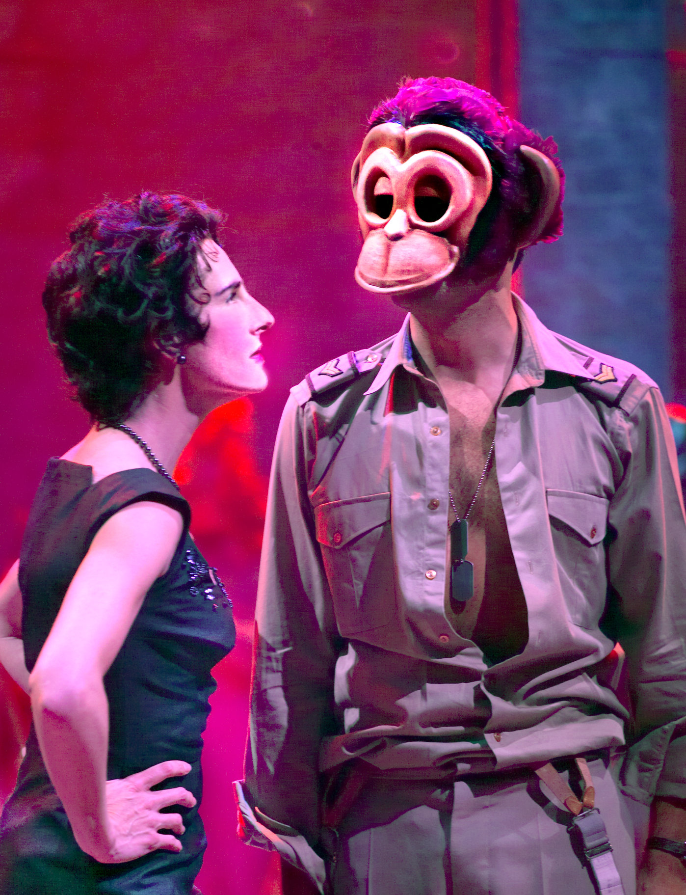 Beatrice talks to Benedick, who wears a monkey mask.
