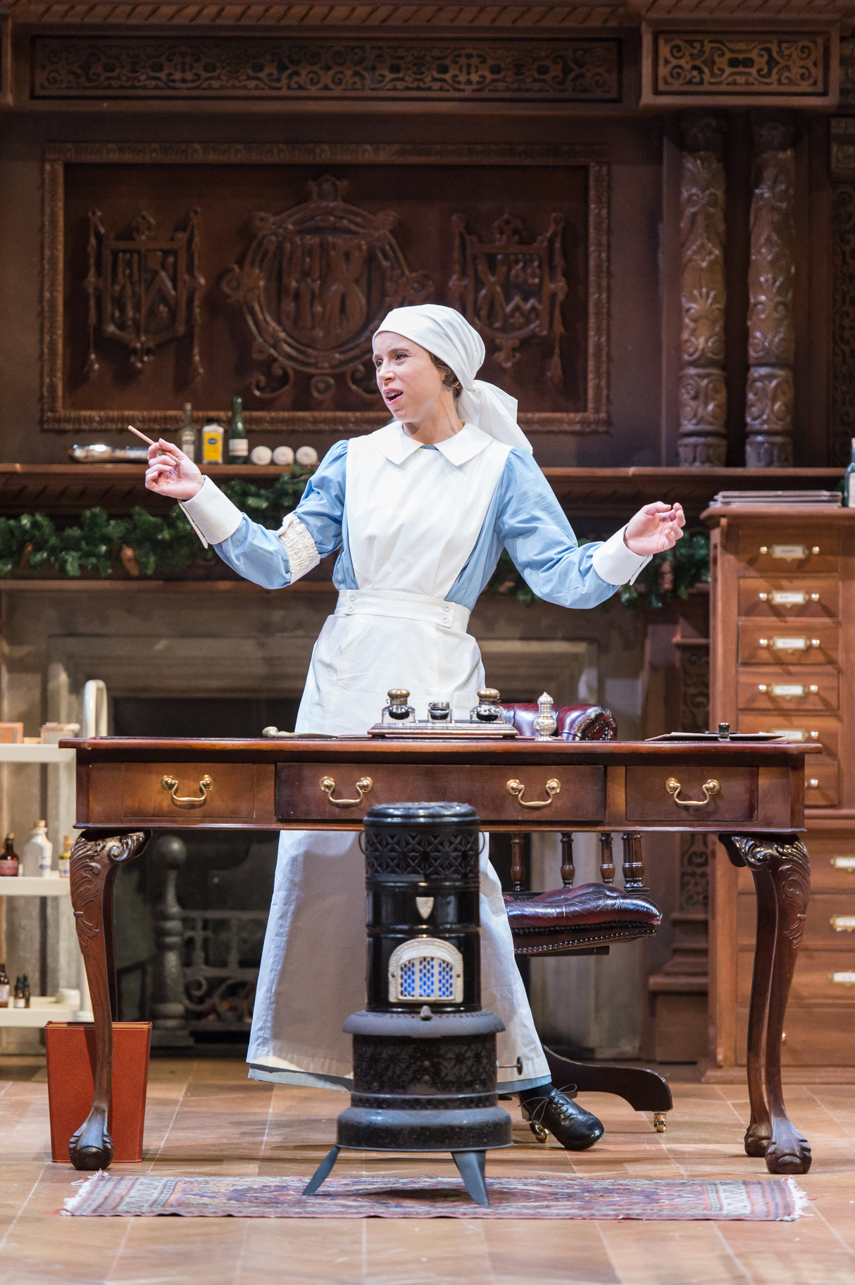 Beatrice in her nurse's uniform stands behind a wooden desk.
