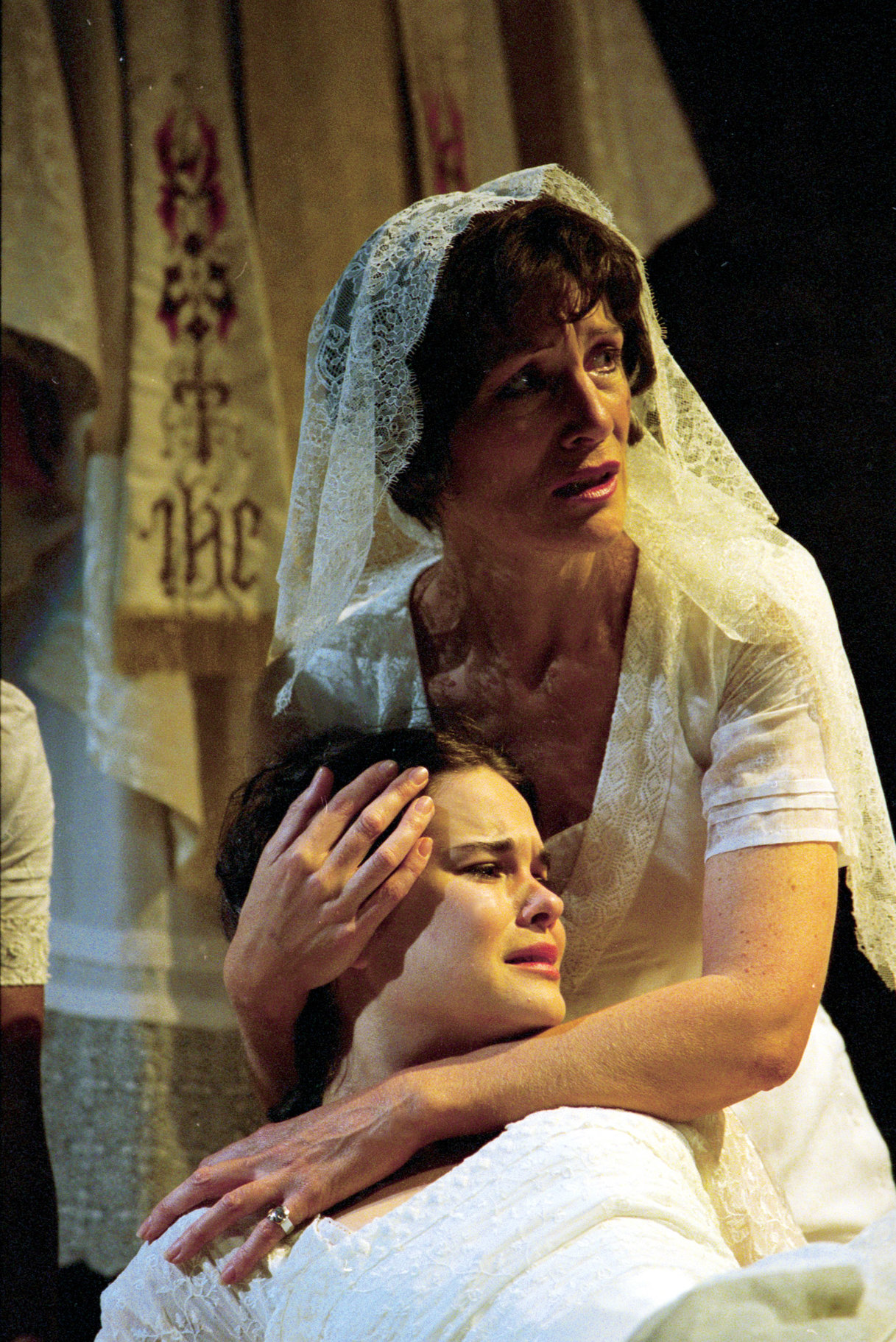 A woman in a white dress and veil holds a crying woman.