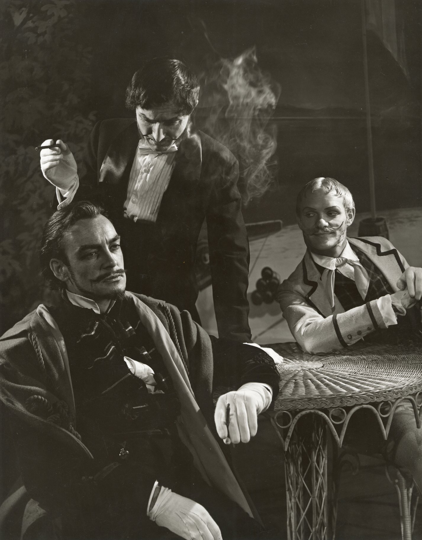 Three men conspire around a round table.