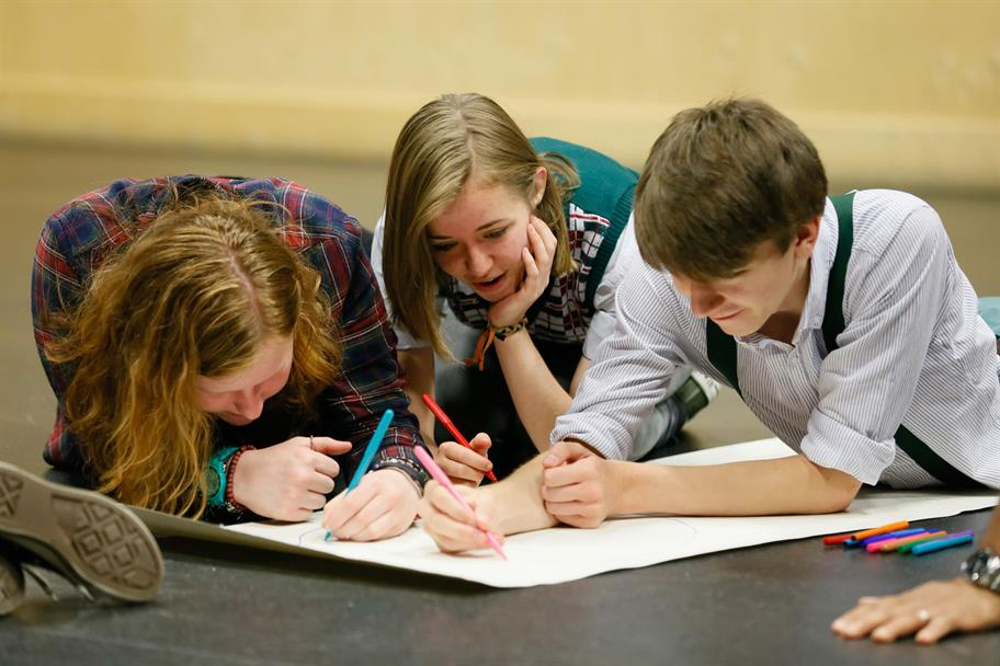 group of 3 students lying on the floor writing with coloured pens