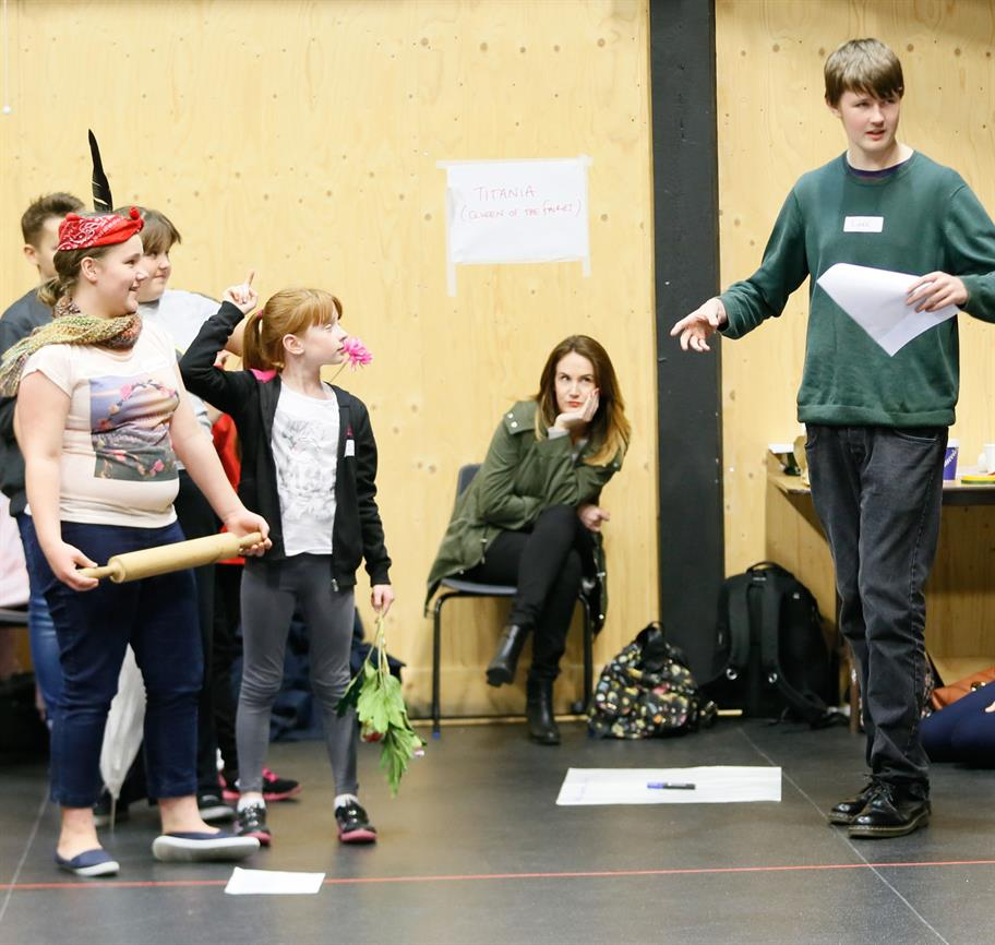 Some children rehearse a scene, carrying props including a plant, rolling pin and script
