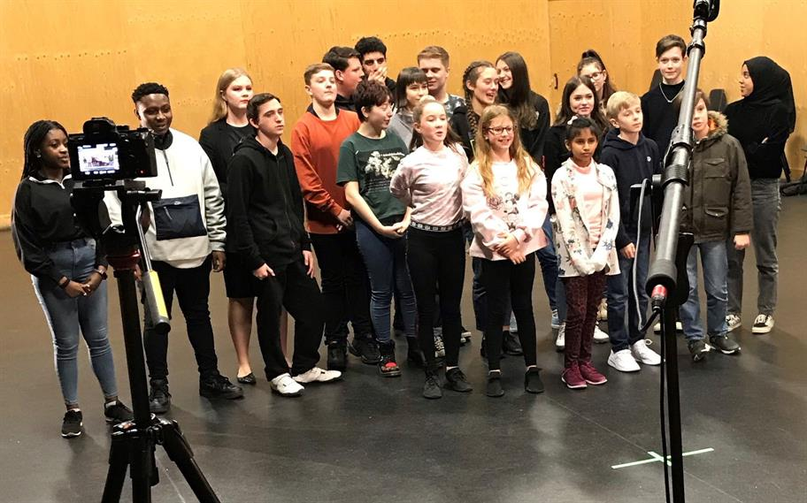 Group of 21 young people standing in a studio together