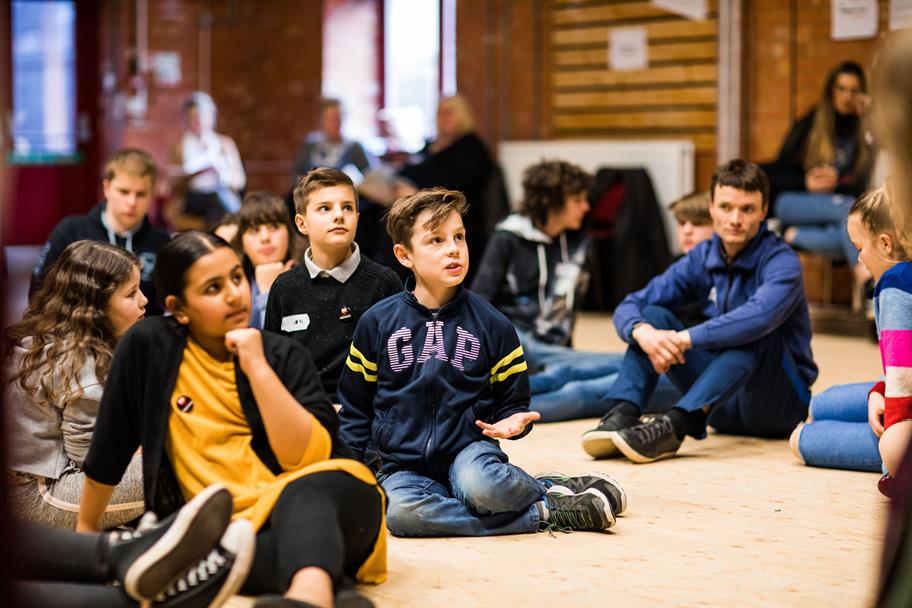 group of young people seated on the floor absorbed in a workshop