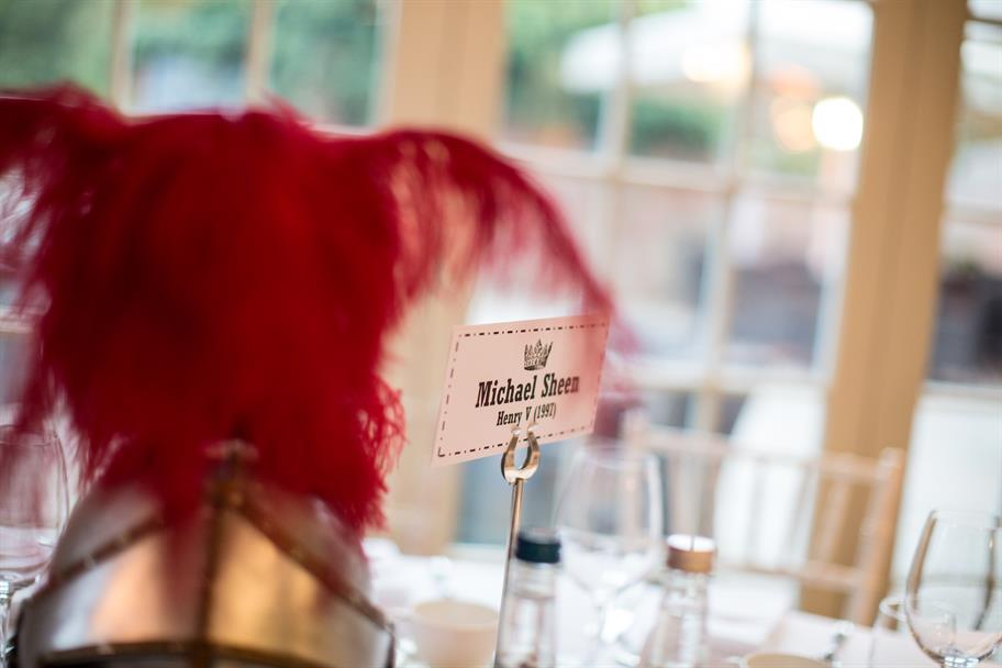 A name tag on a round dinner table reading: Michael Sheen, Henry V, and a metal helmet with bright red feathers